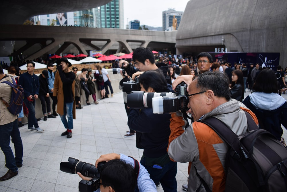 group of photographers holding DSLR cameras in event during daytime