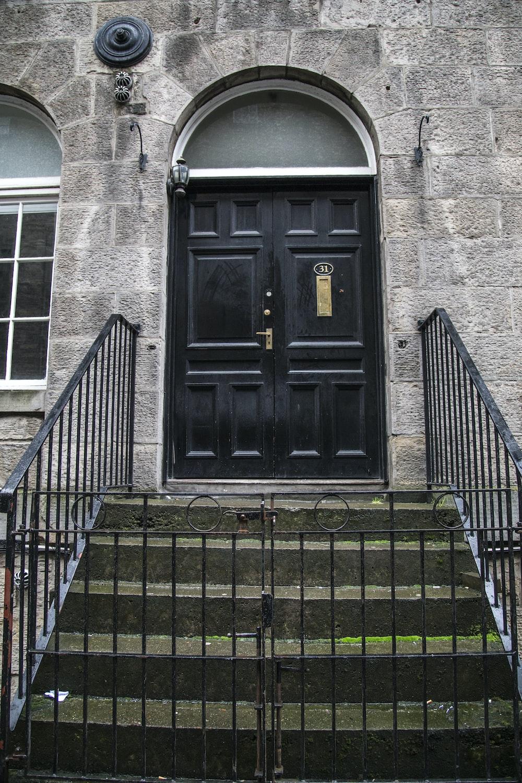 black wooden door on gray brick building
