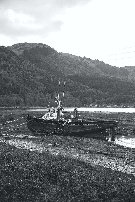 grayscale photo of boat on sea near mountain