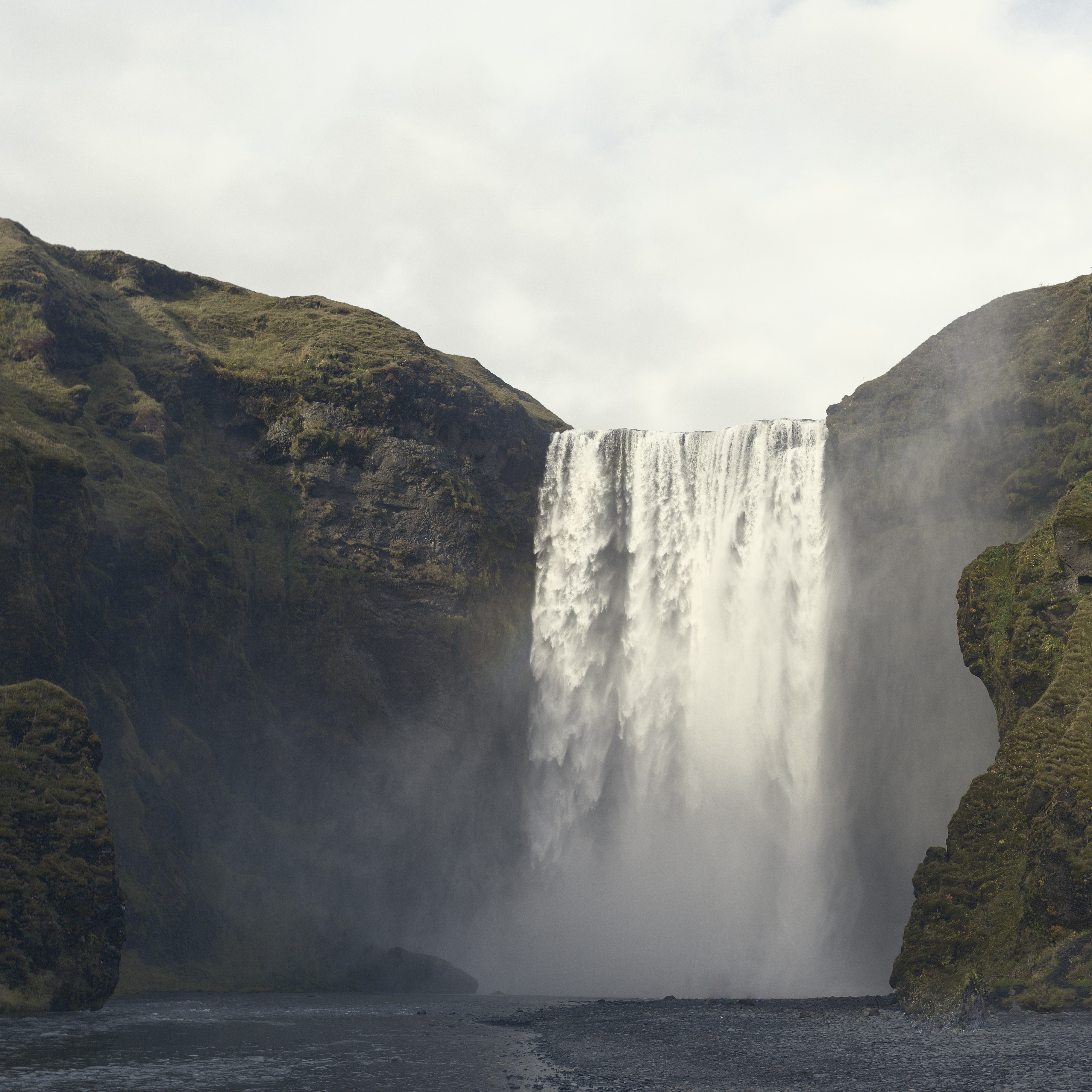 A large waterfall streaming from a rocky mountain in Iceland