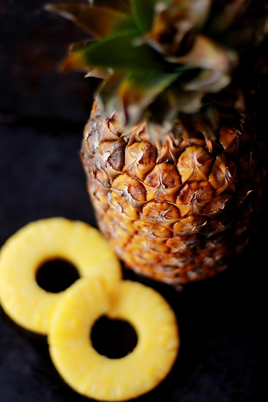 brown pineapple fruit beside slice fruits