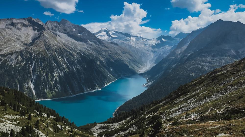 body of water between mountain range at daytime
