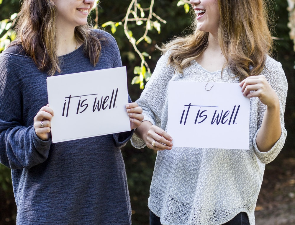 """Two women holding up pieces of paper that say """"It is well,"""" while looking at each other and smiling."""