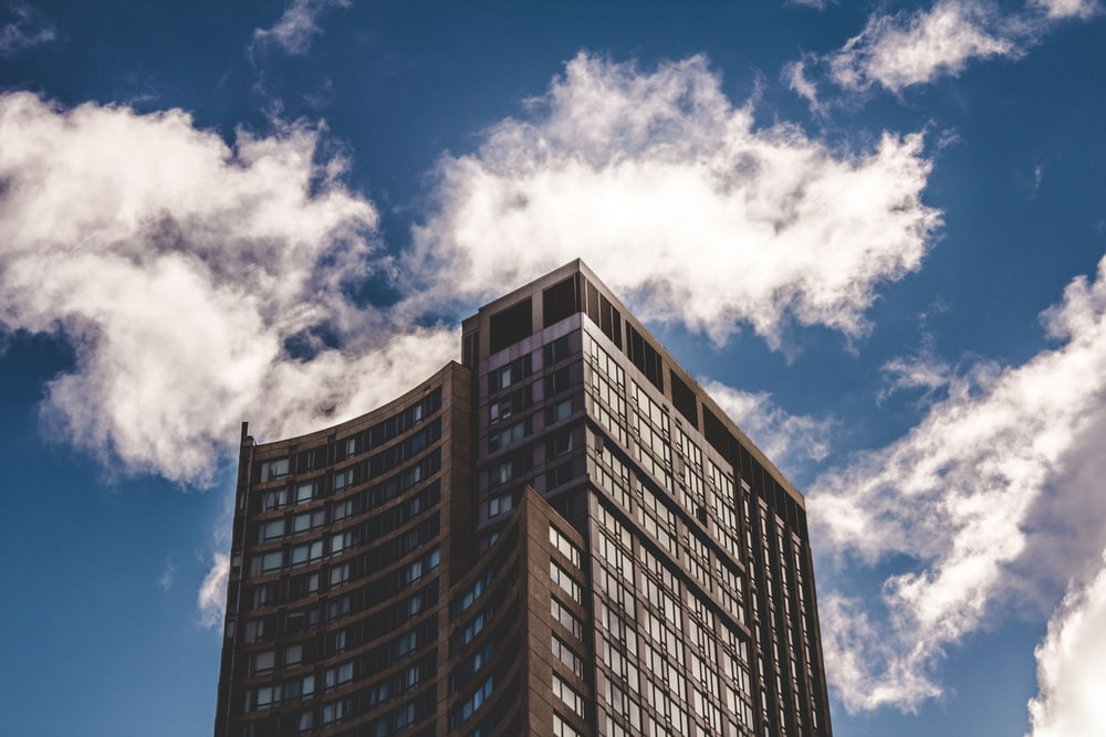 brown high-rise building under clouds during daytime