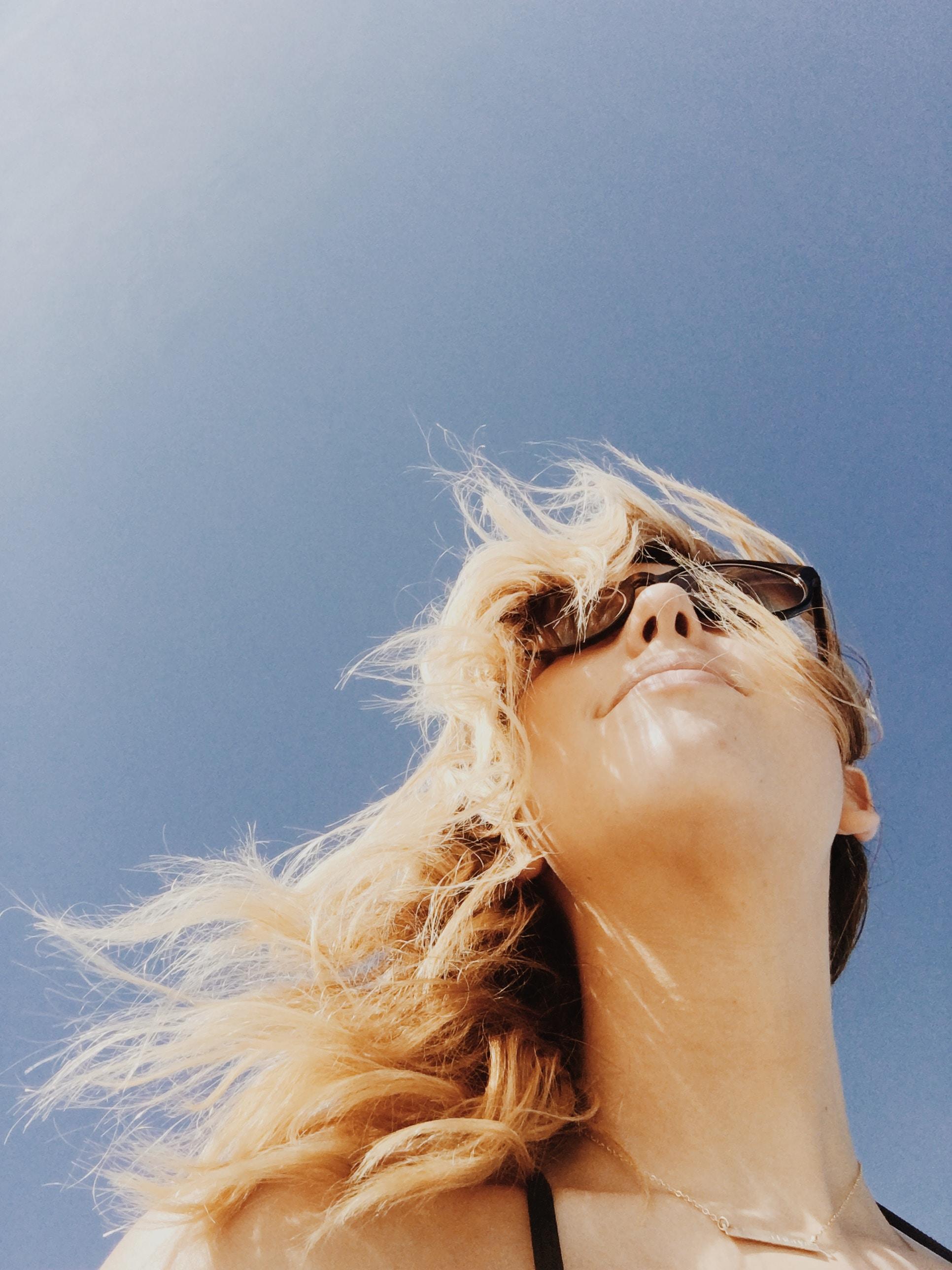 A happy blonde girl wearing glasses outside.