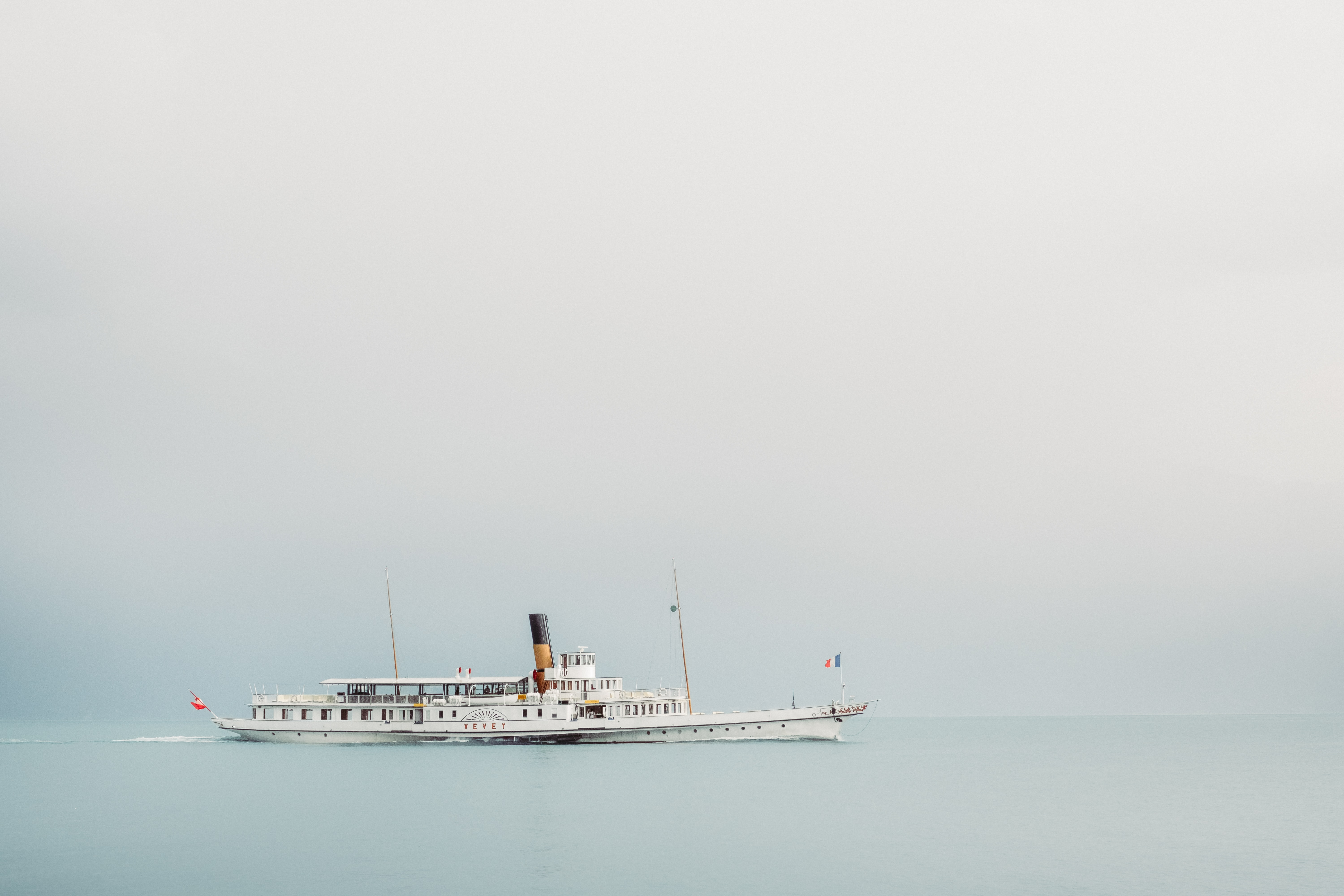 A beautiful steamboat gliding over the calm ocean in Vevey on a foggy day