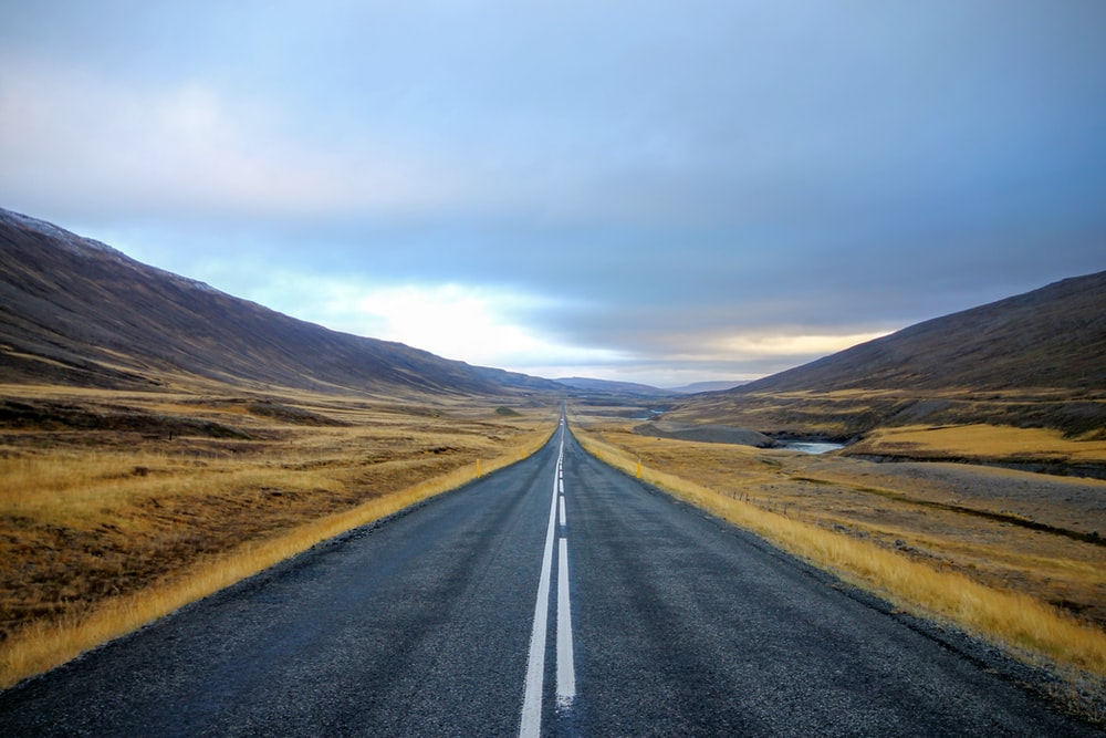 landscape photography of black asphalt road with white line surrounded by brown grass field during daytime