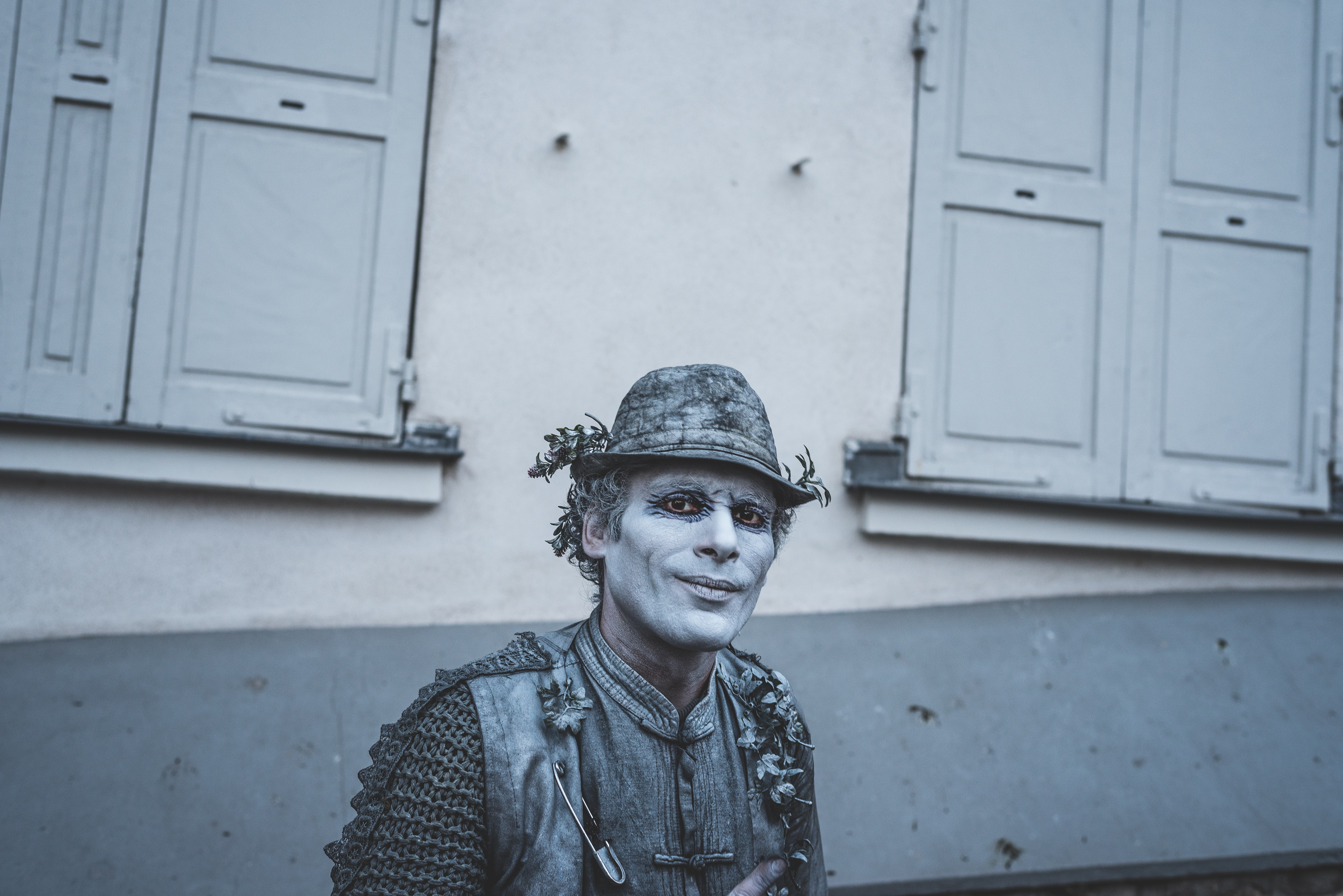 A street performer with a gray costume outfit and face paint.