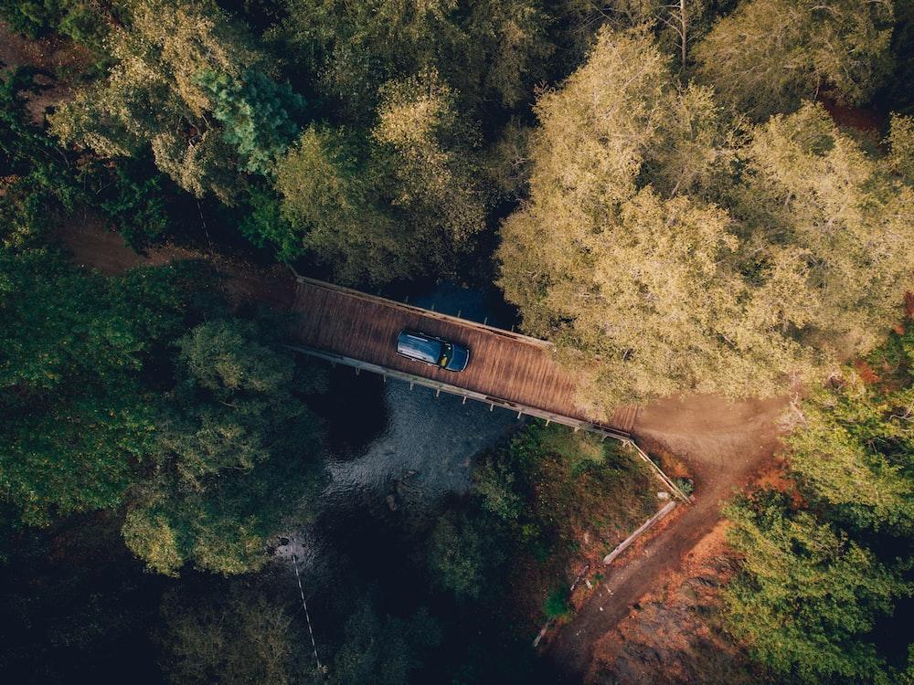 aerial photo of blue car crossing bridge