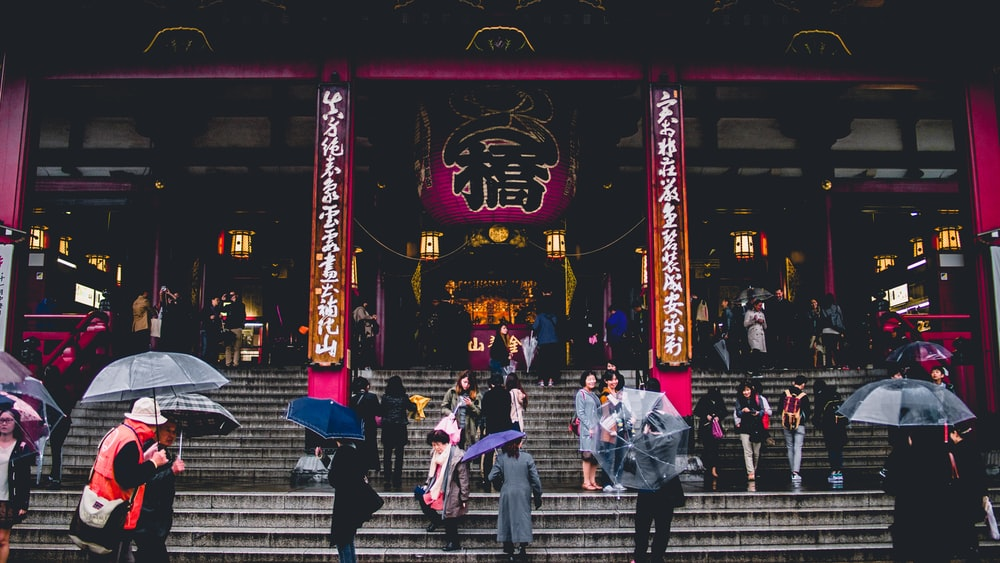 people walking on concrete stairs in front of temple