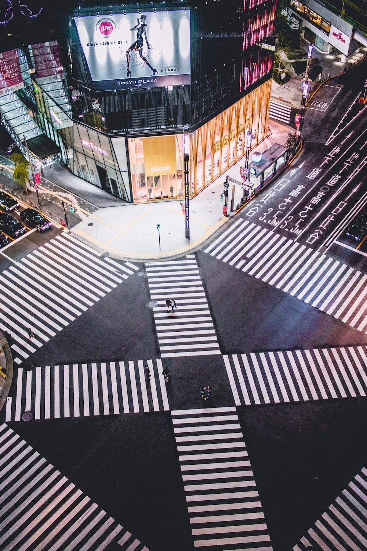 people walking on pedestrian lane in between building during nighttime