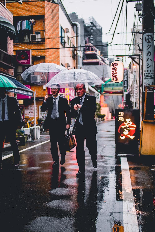 two men in black suit holding transparent umbrellas walking in the street