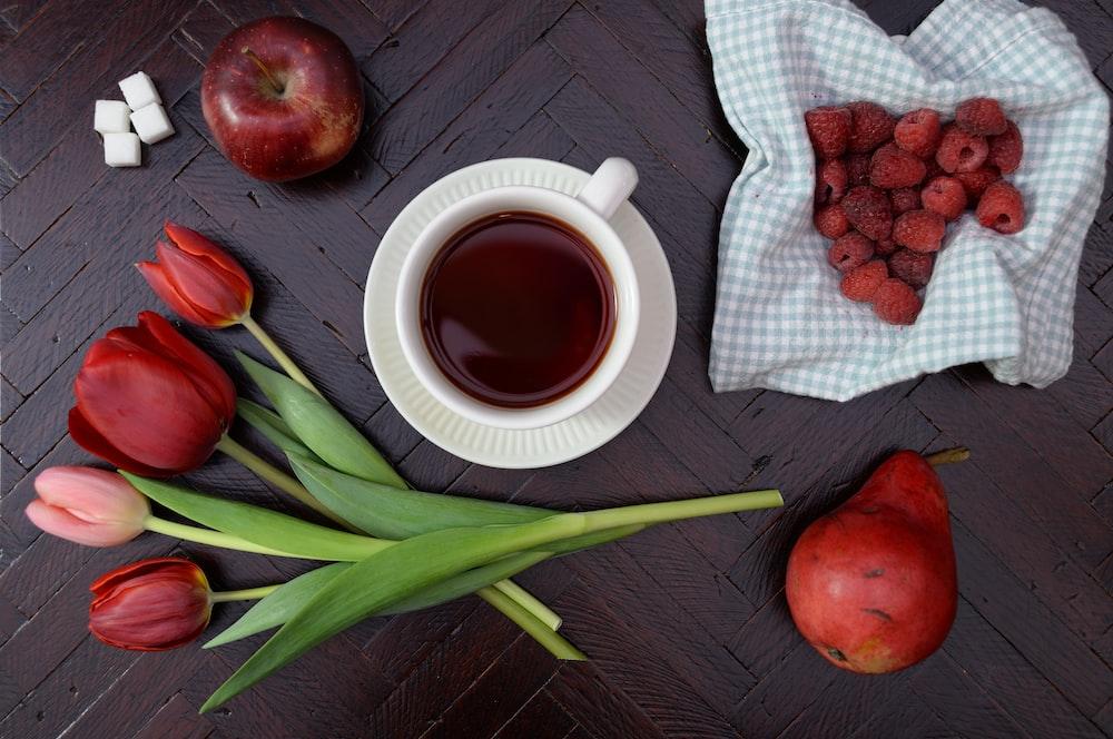 teacup on saucer near apple and tulip flower