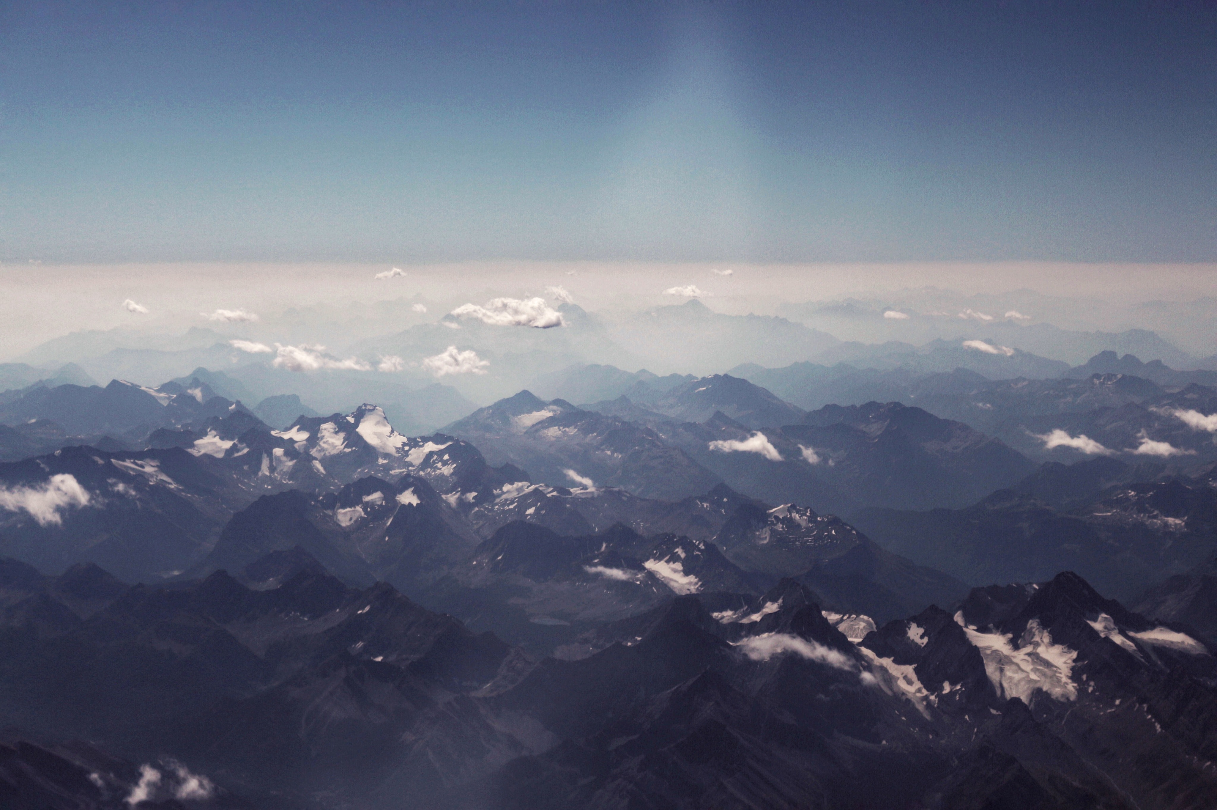 An aerial shot of a mountain range with small fluffy clouds between its peaks