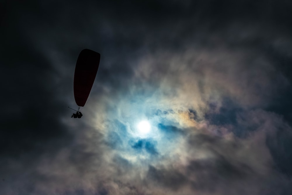 low angle photo of silhouette of man with parachute