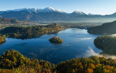 island surrounded by water and mountains at daytime slovenia zoom background