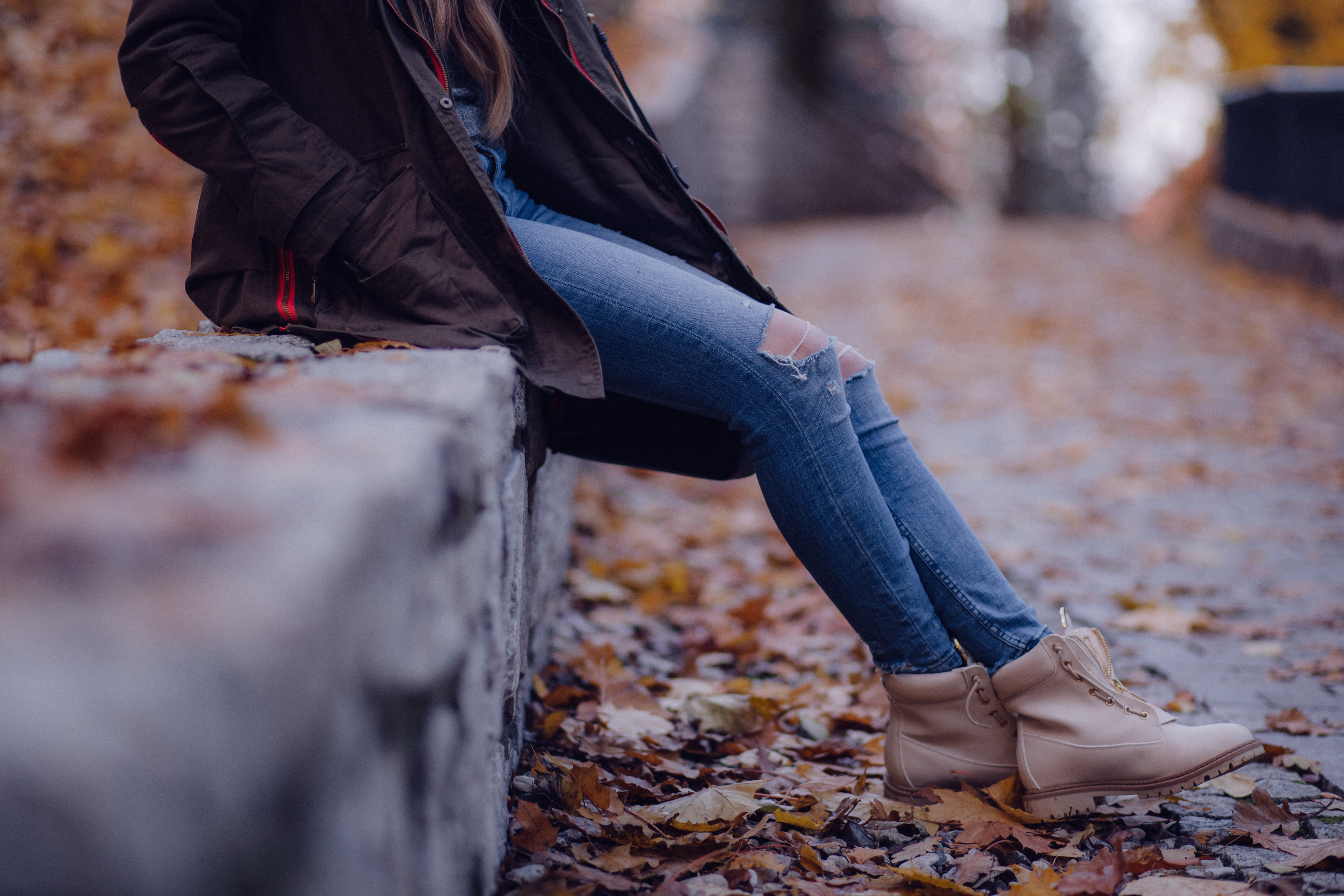 Low shot of woman wearing jeans and a fall coat