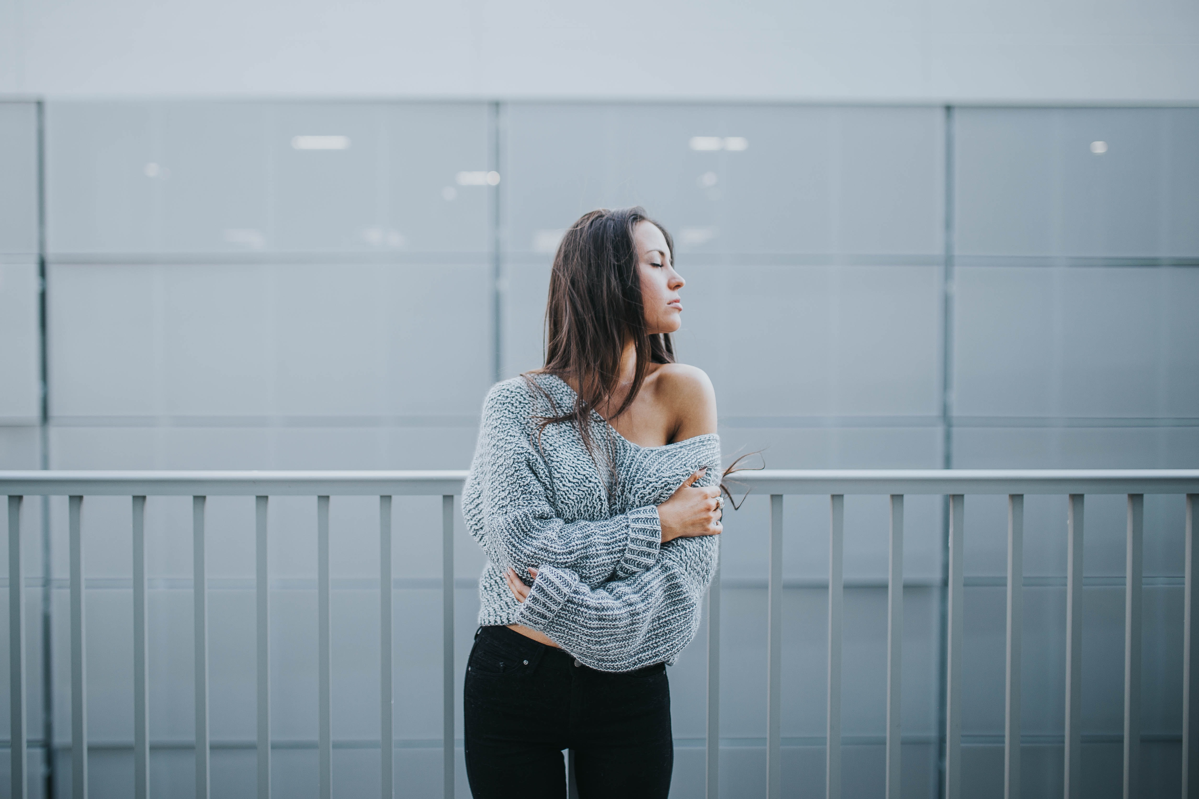 A woman in an off-the-shoulder sweater stands in front of a white railing and white wall