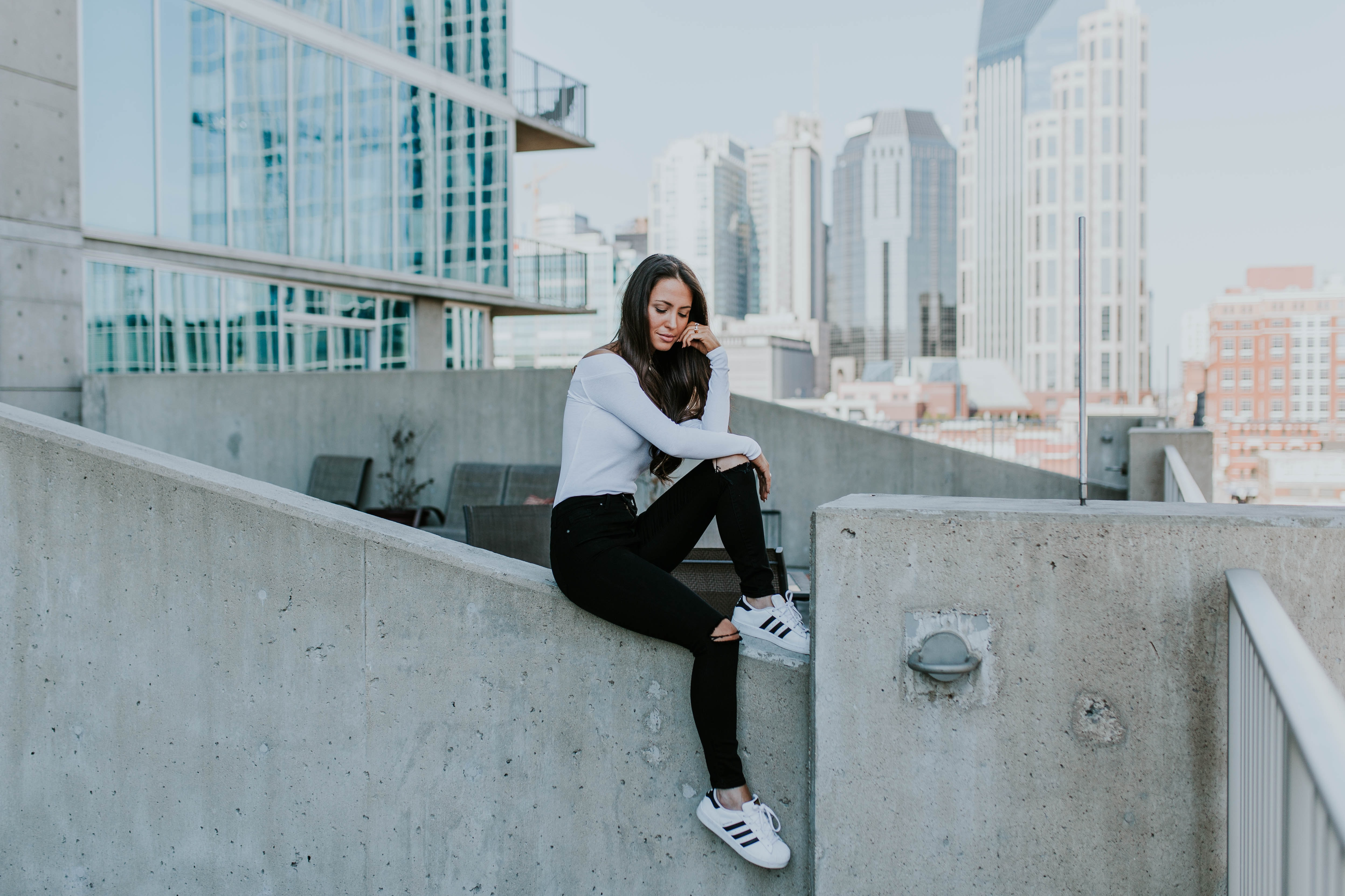 A young woman in ripped jeans posing while sitting on a concrete ledge in a city