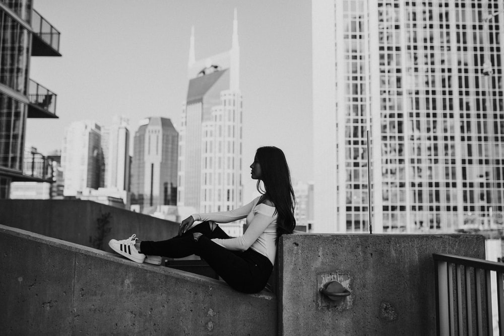 grayscale photography of woman sitting