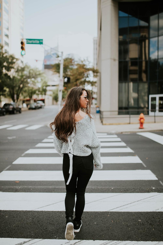 woman looking towards her right while walking along pedestrian lane during daytime