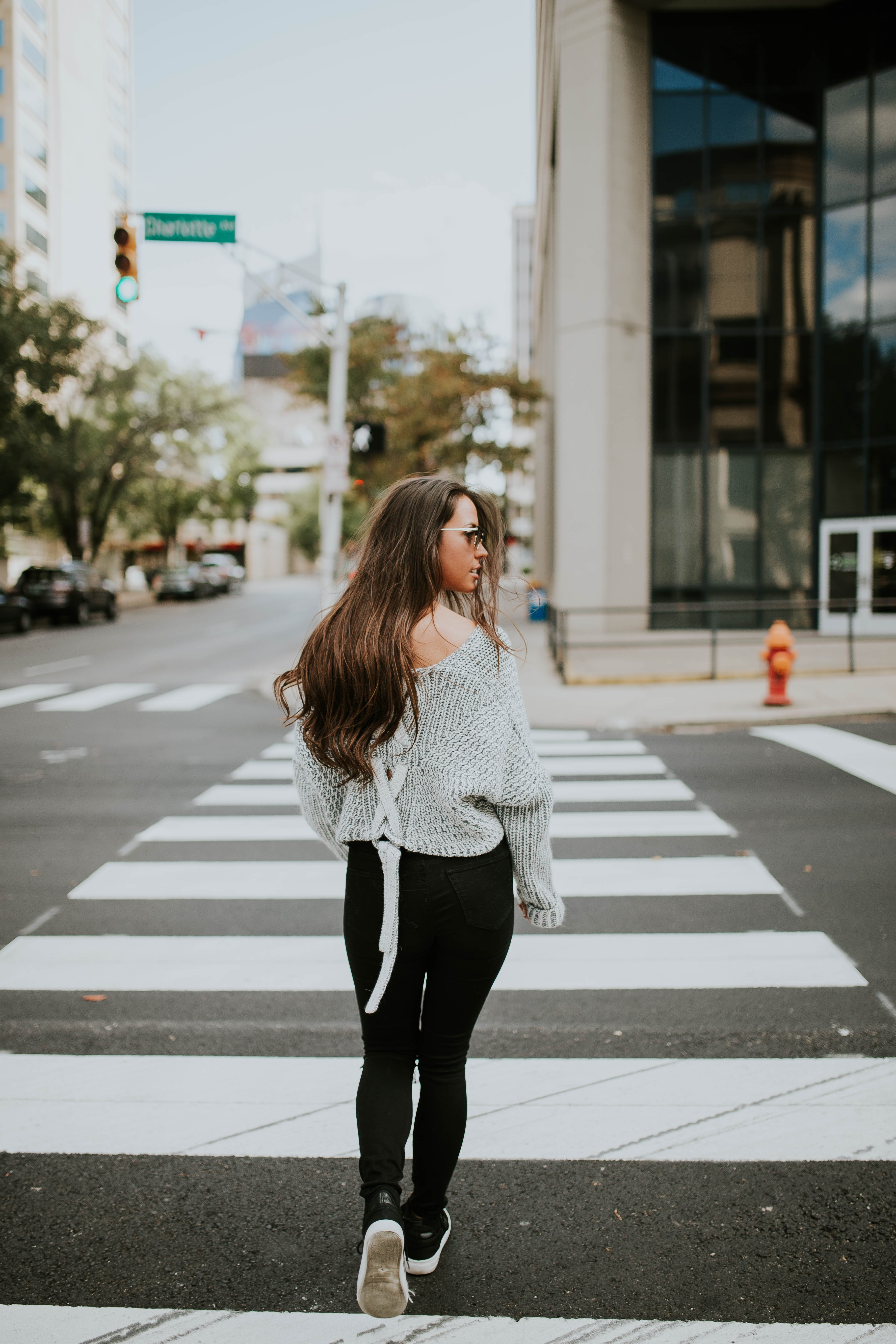 woman looking towards her right while walking along pedestrian lane during daytime