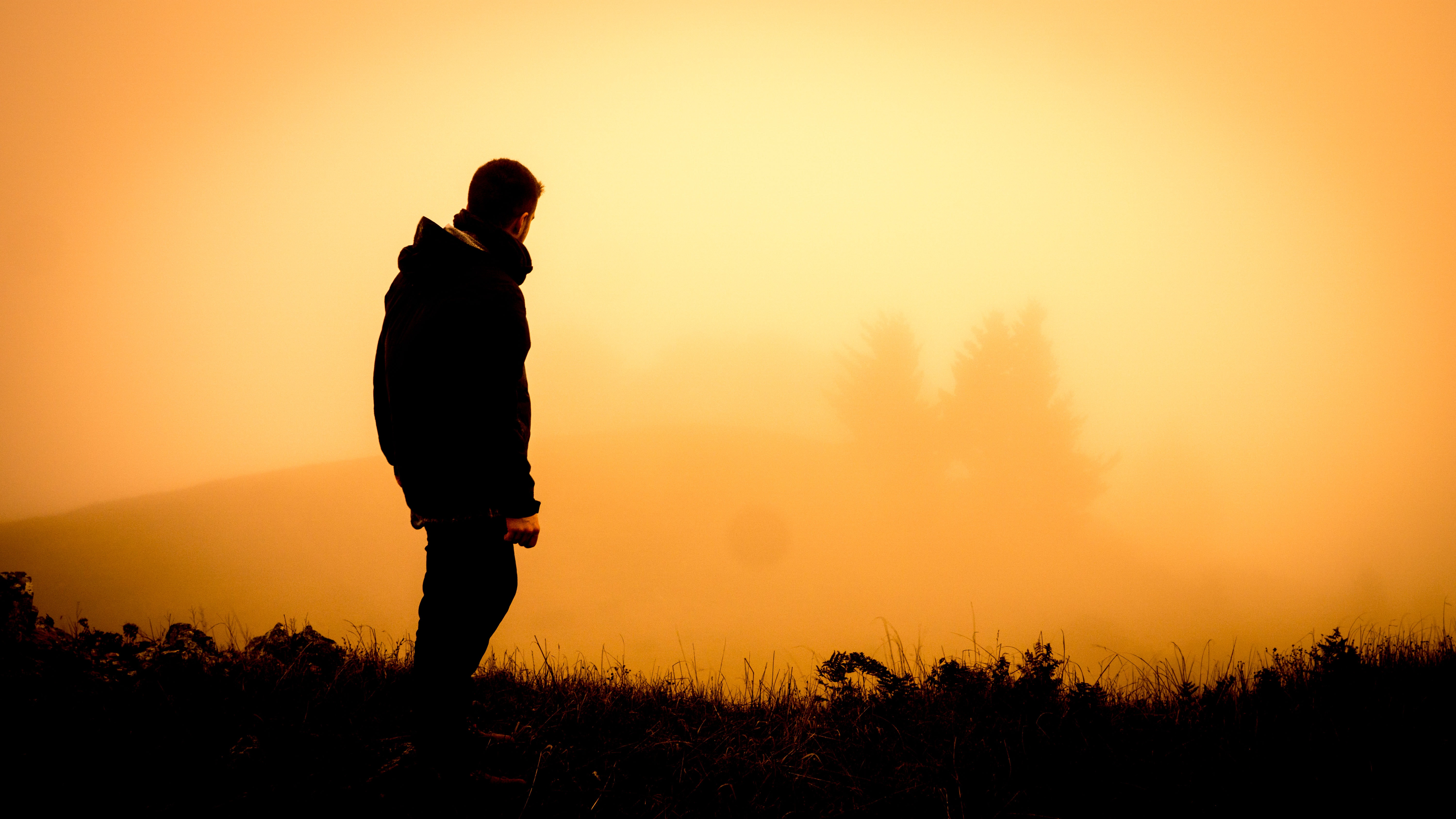 Silhouette of a standing man, against a hazy orange sunset, gazing at distant trees through haze