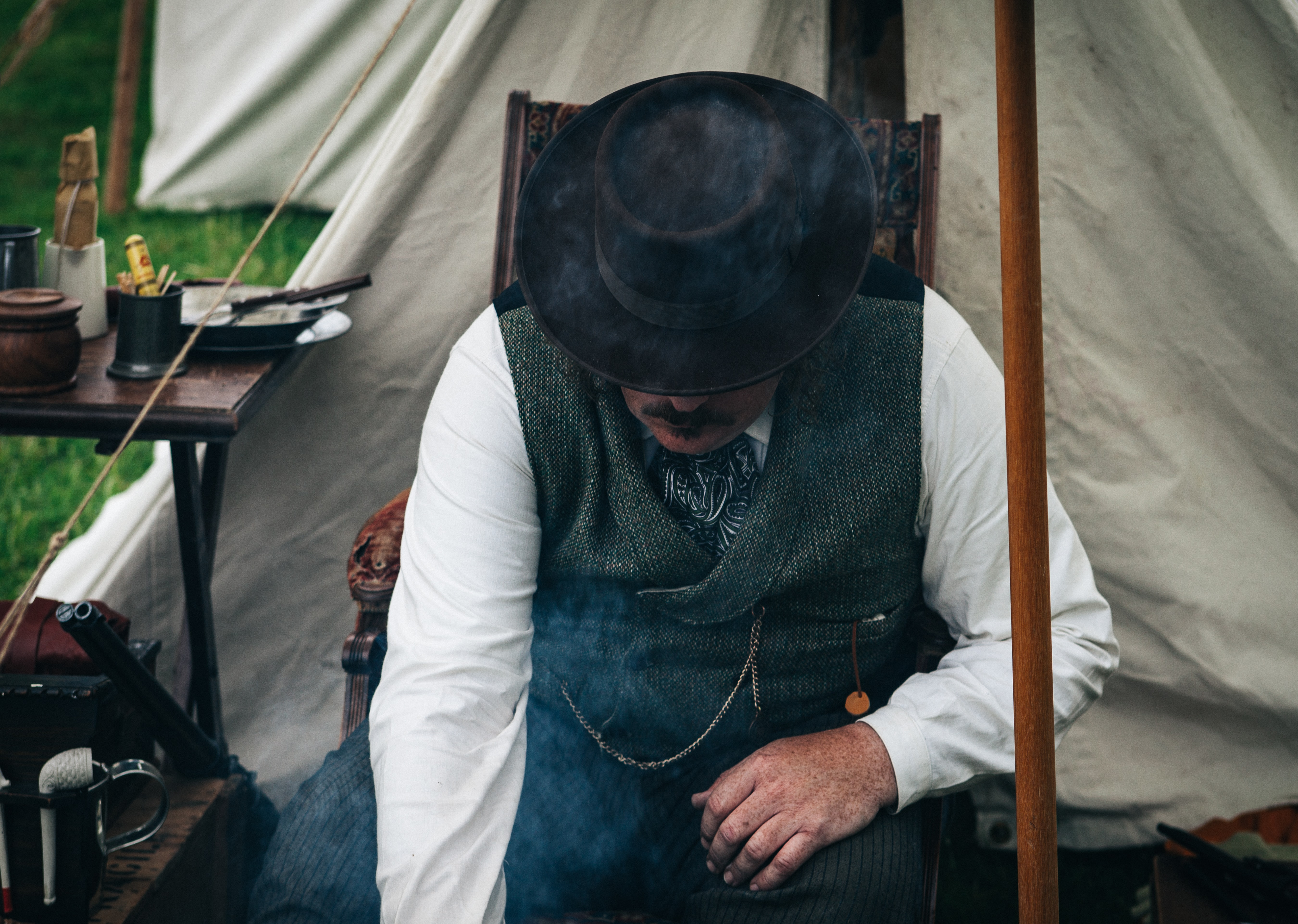 A man with a mustache bends down while sitting on a chair inside a tent