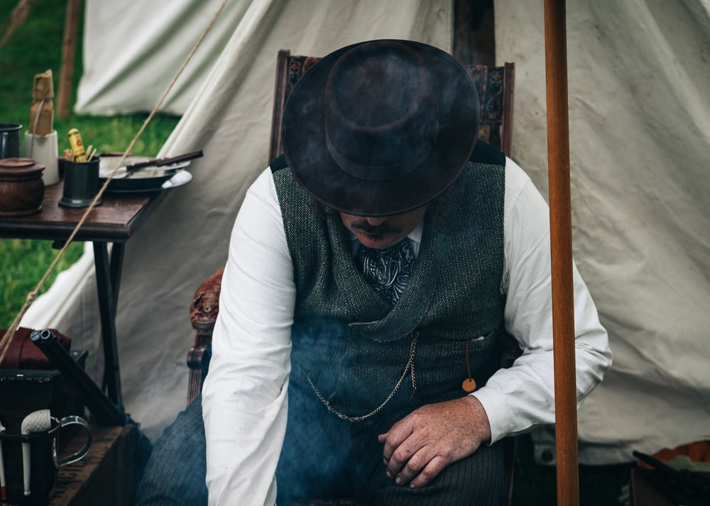 man sitting on chair beside tent