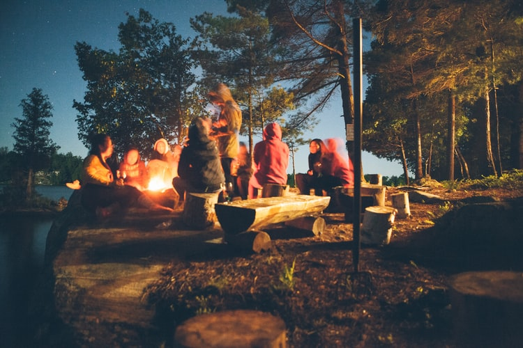 sustainable travel - camping at night with friends around fire