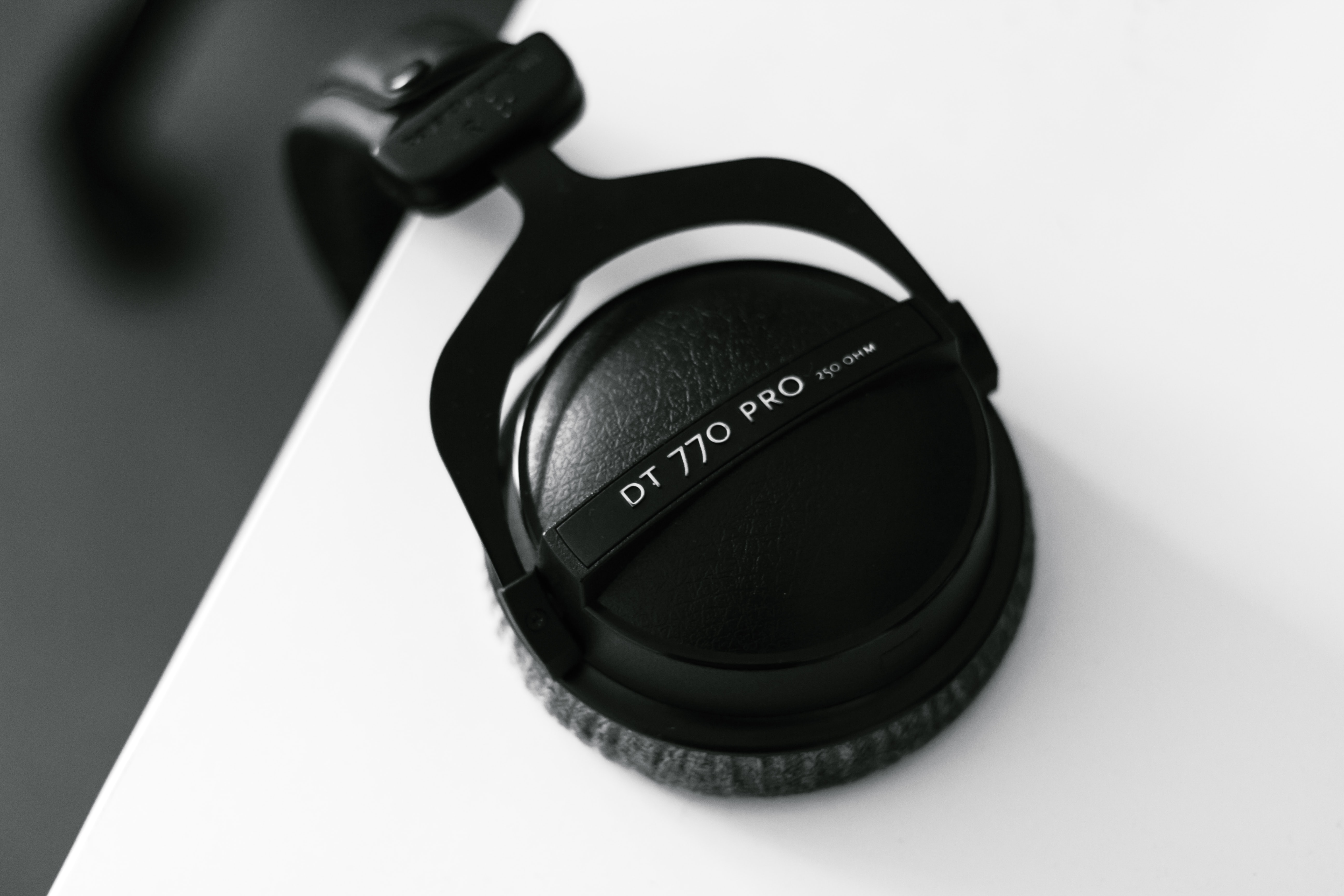 Close-up of black headphones hanging from a white surface