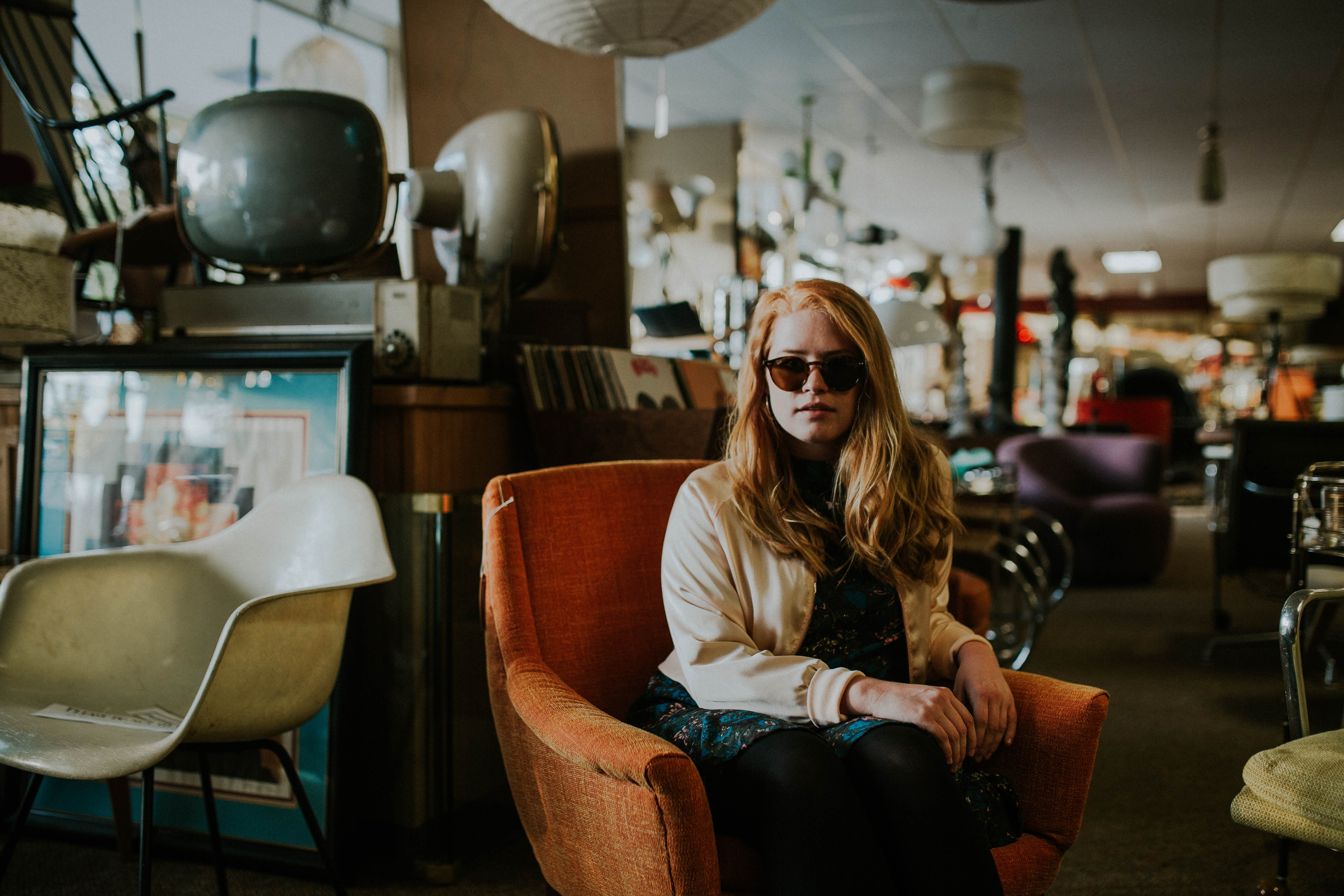 A woman in sunglasses sits on an orange chair inside a secondhand store