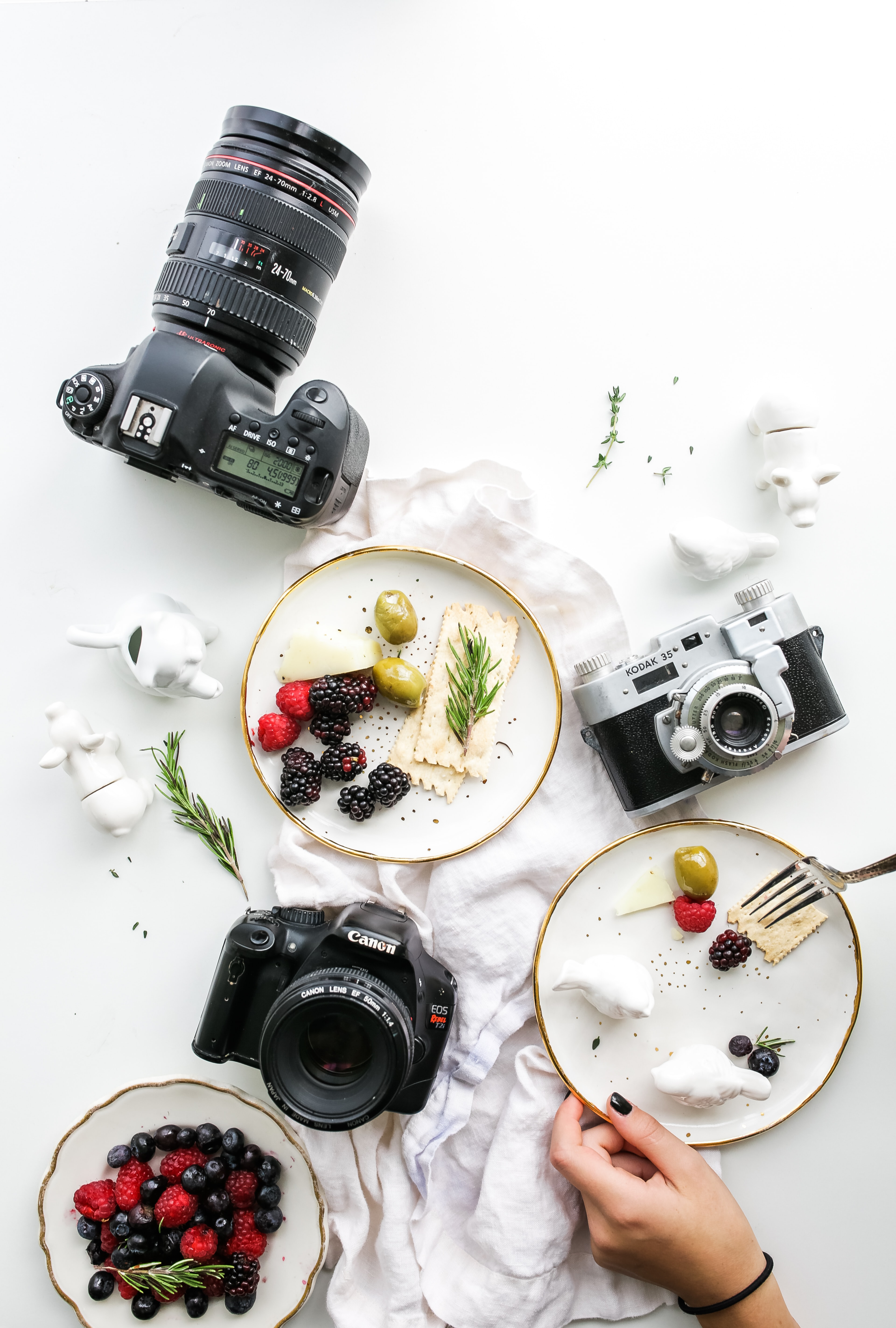 An overhead shot of plates with fruit and crackers and various cameras