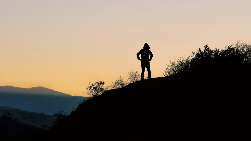 silhouette of person on top of hill during golden hour