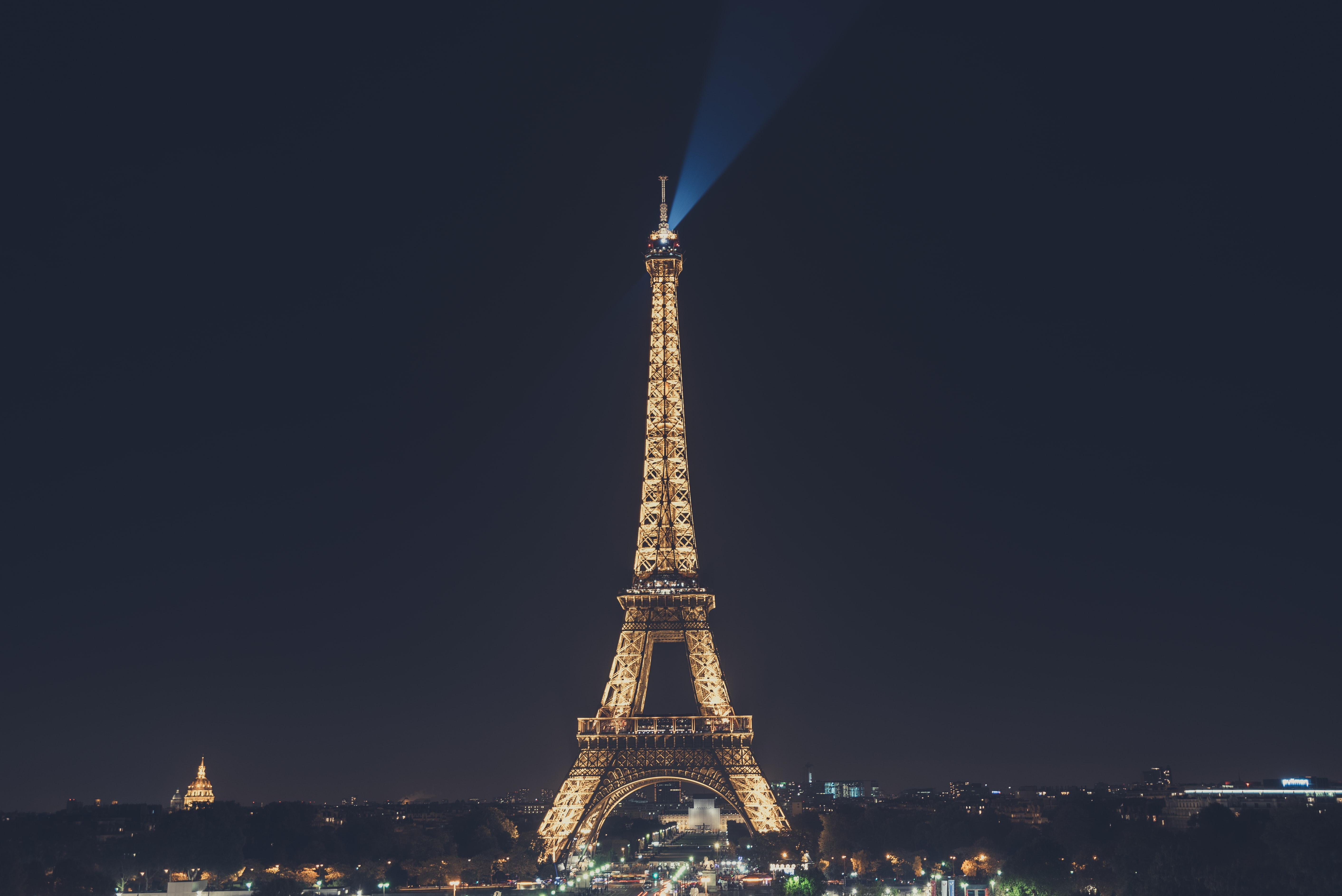 The landmark Eiffel Tower and its architecture illuminated at night