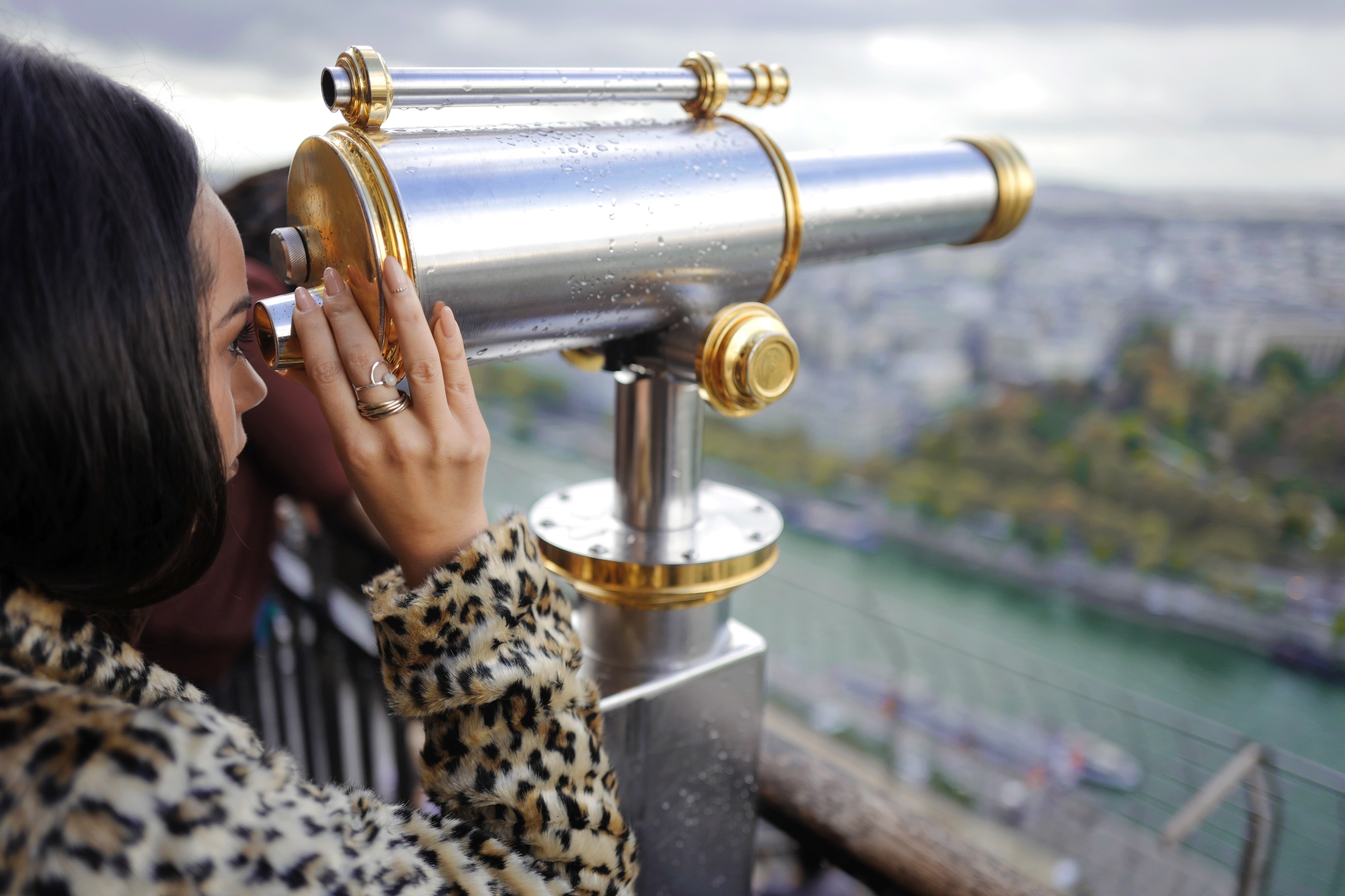 A fashionable woman looking over a river through a viewfinder telescope