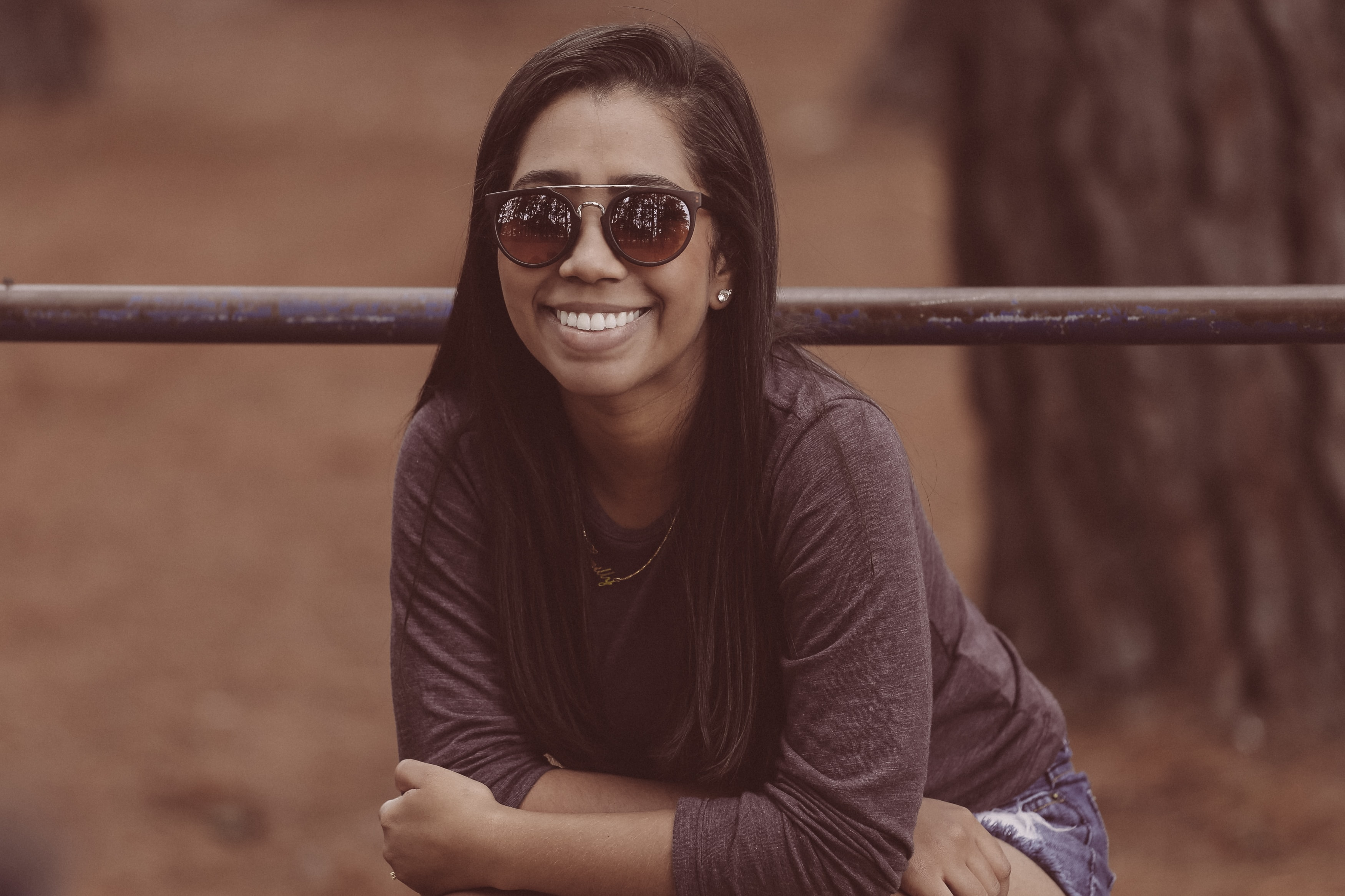 Woman in sunglasses smiles in front of a railing in Parque da Cidade