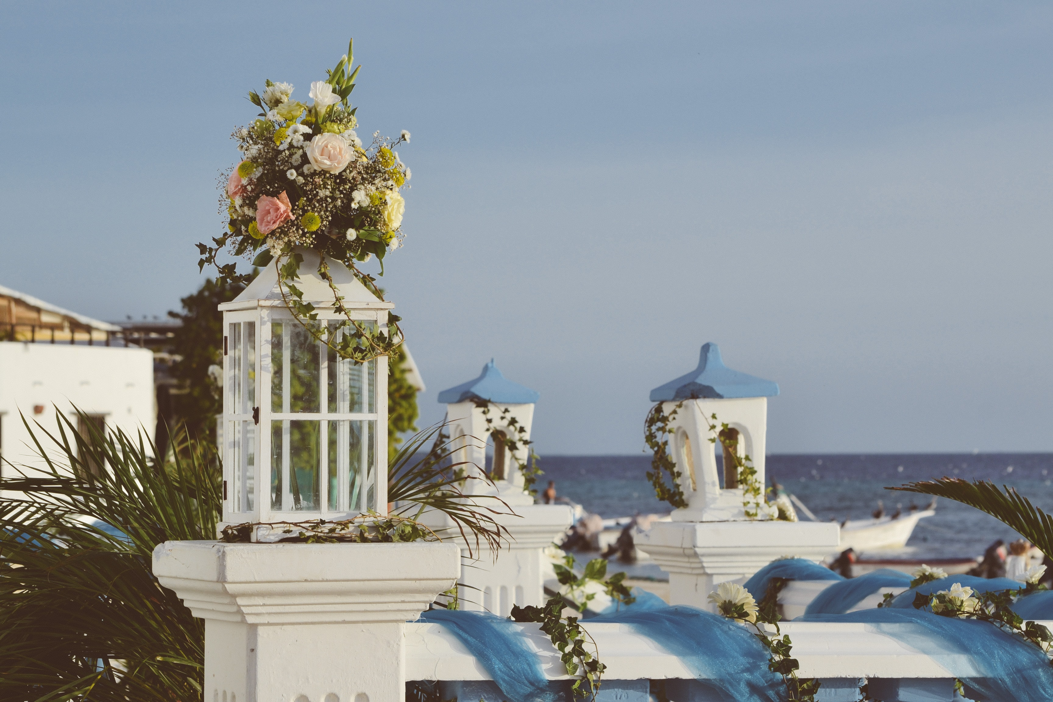 A bunch of flowers on top of a balustrade in a Mediterranean setting with the sea in the background