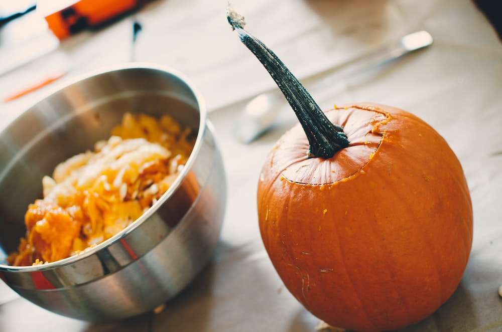 orange squash on table beside steel bowl