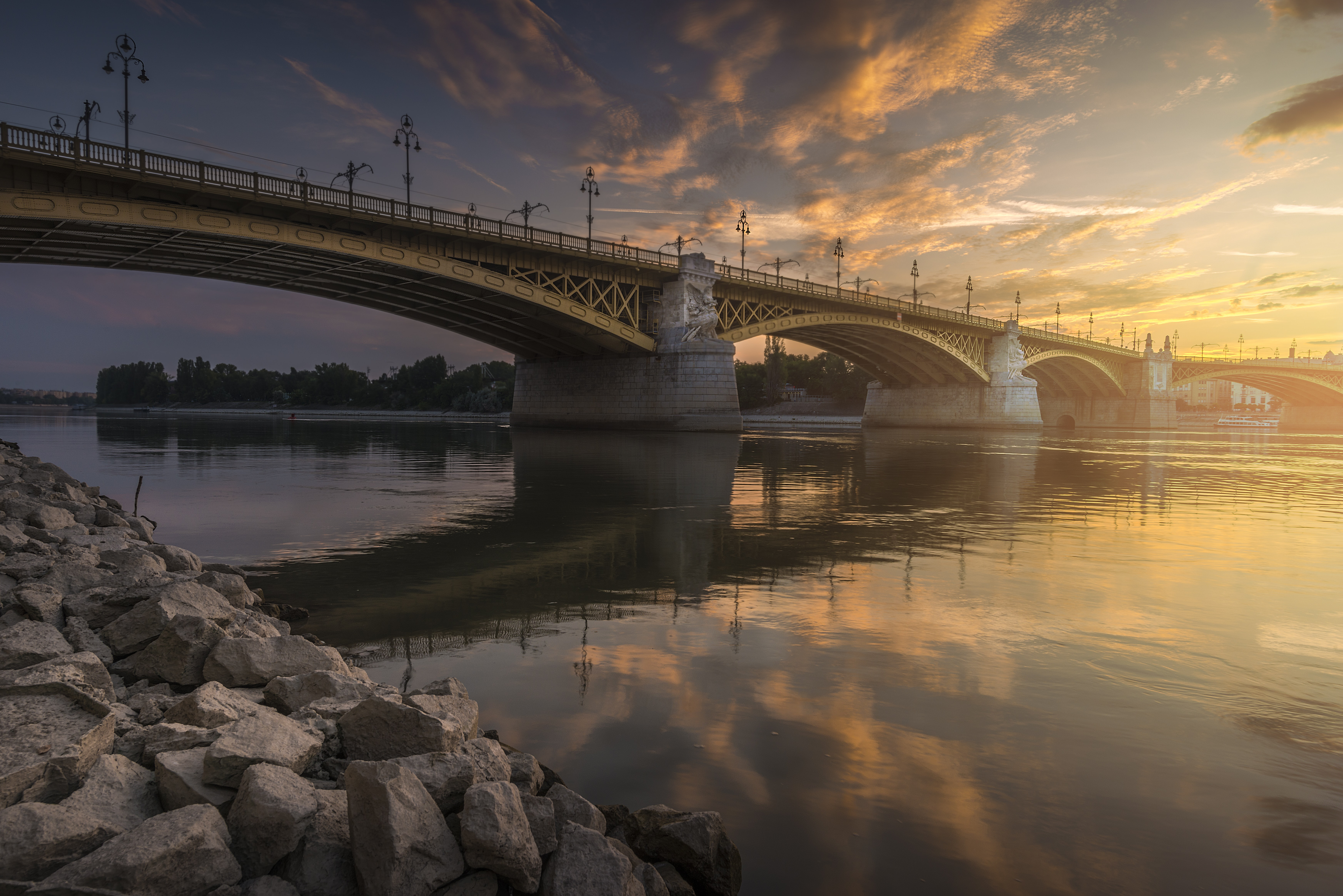 The steel arch bridge and sky reflect into the still river in Budapest during sunrise-or-sunset