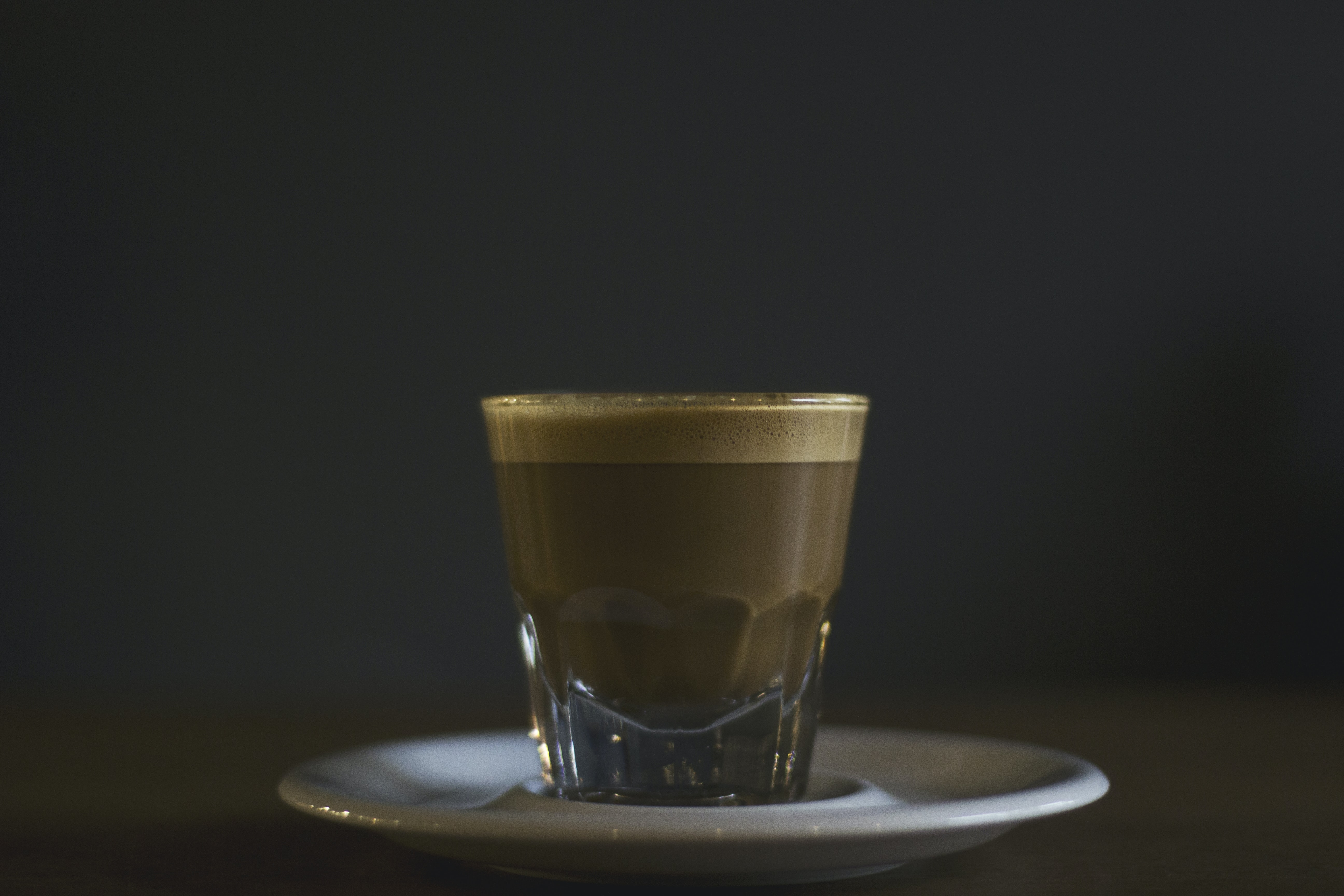Espresso in a clear glass on a white saucer with a black featureless background