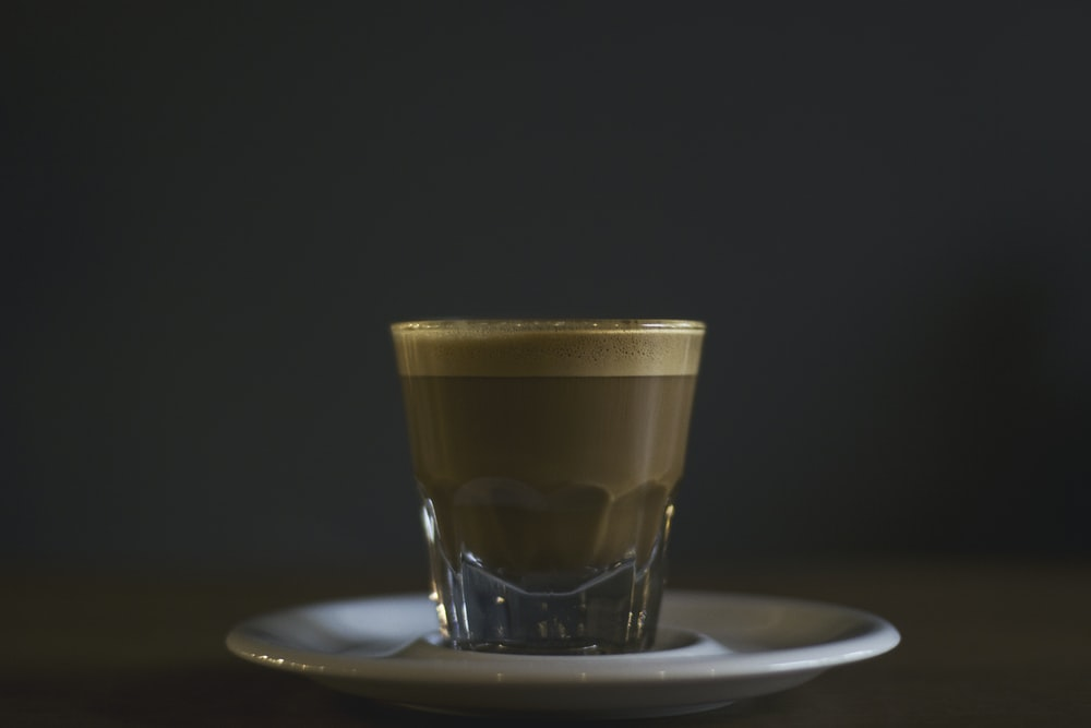 coffee filled rock glass on saucer
