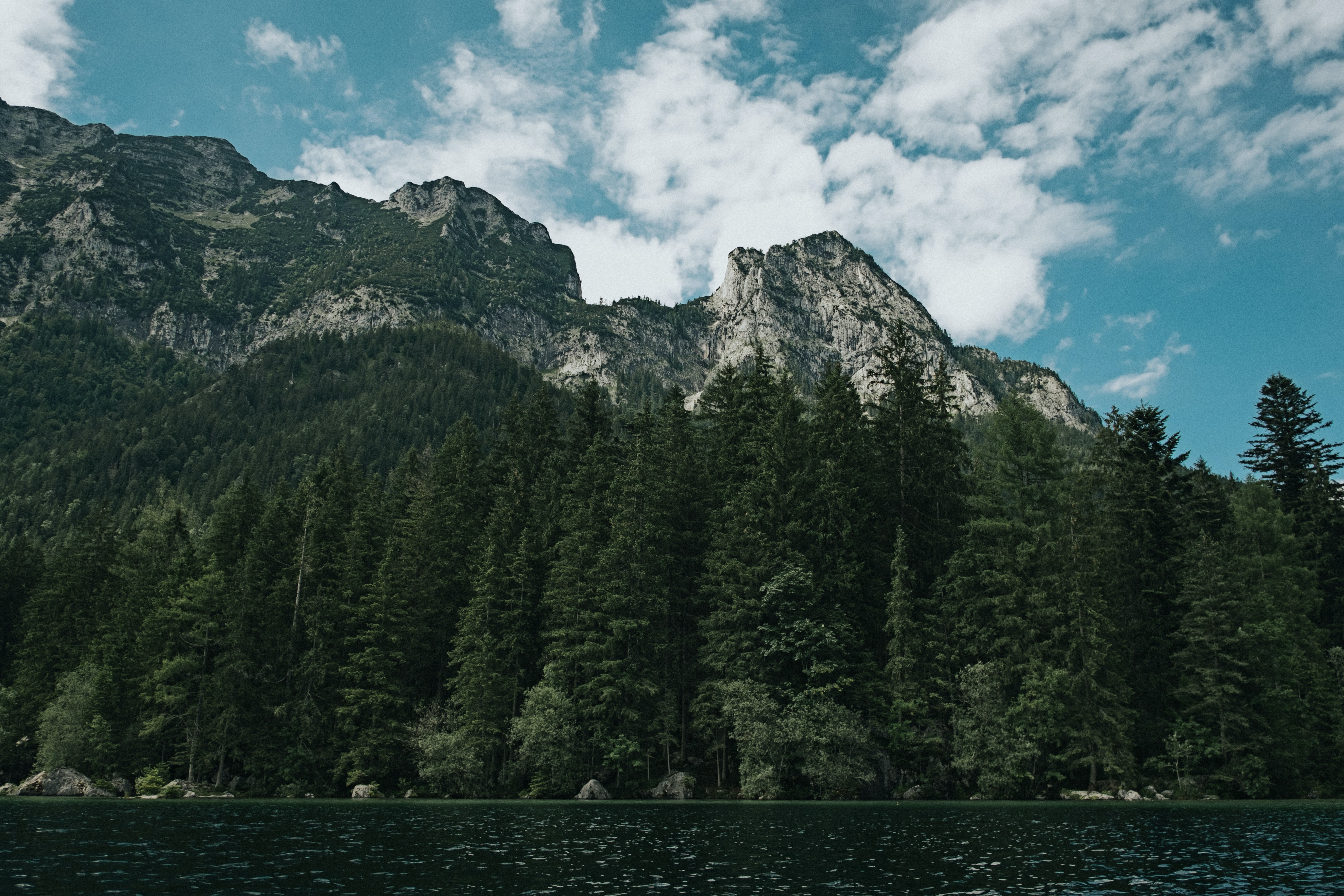 A forest-surrounded lake at the foot of a craggy mountain range