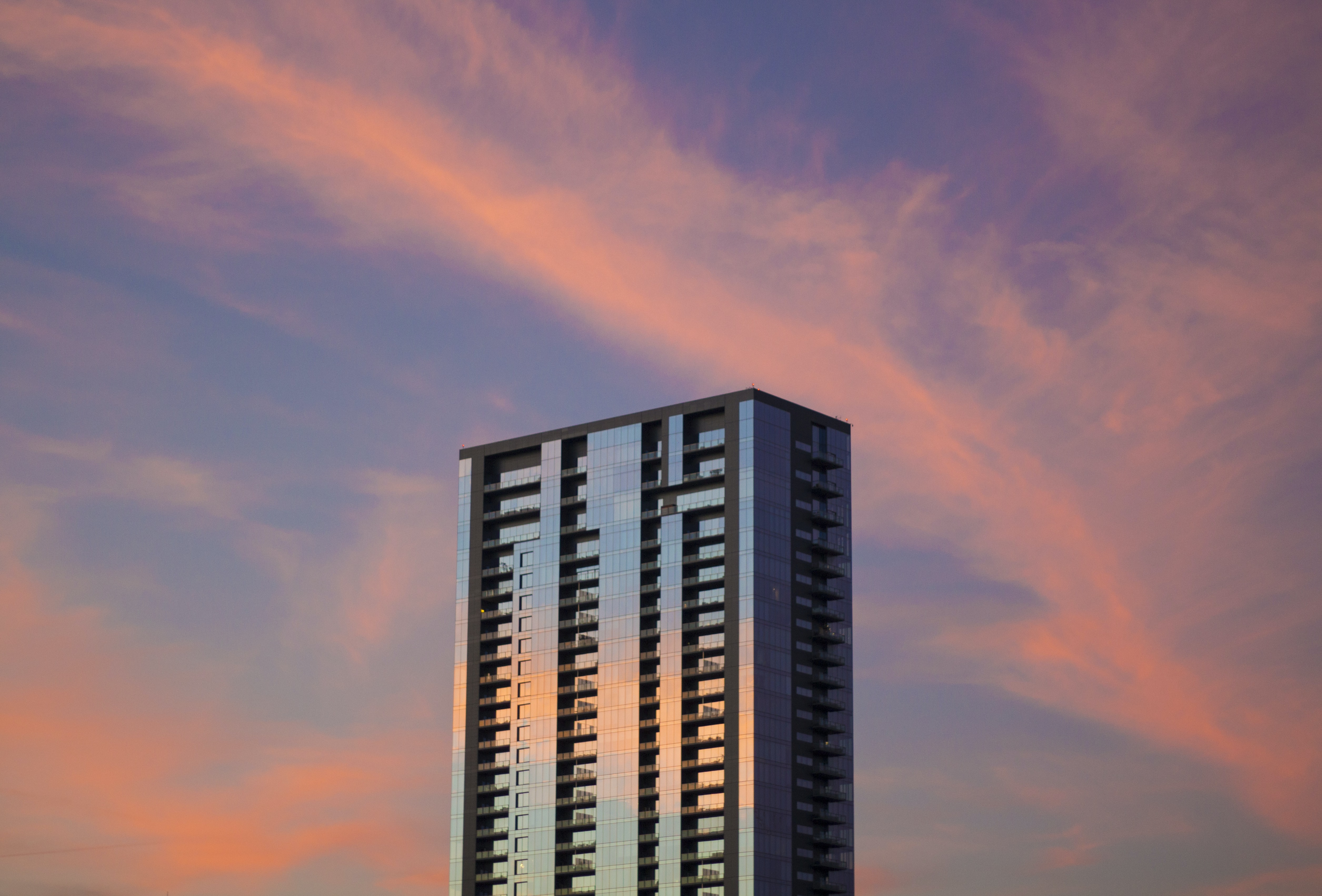 A skyscraper reflecting the purple and pink cloudy sky at sunset in Austin