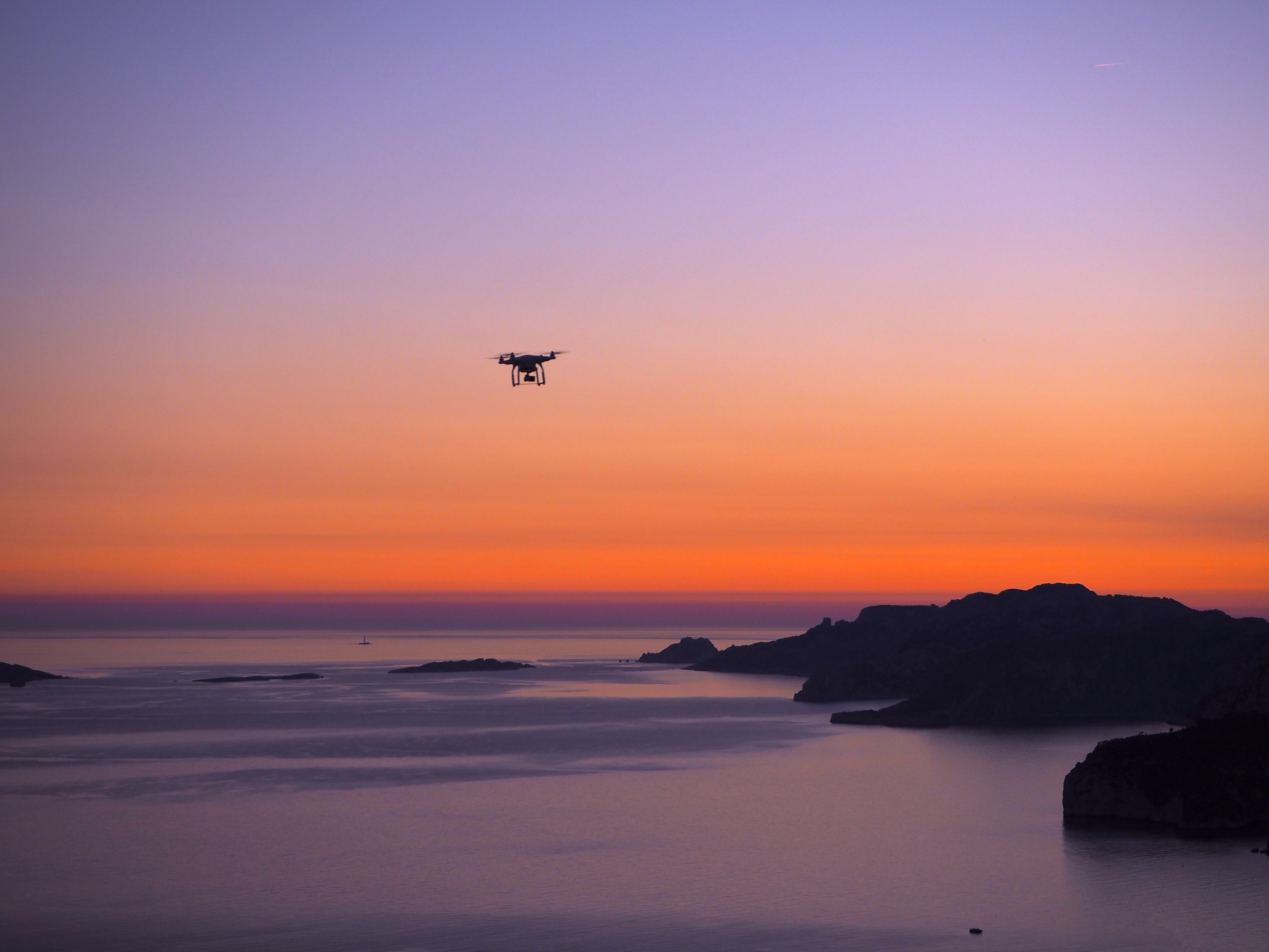 A drone hovering over the water and rocks of La Ciotat with an orange and purple sunset in the background