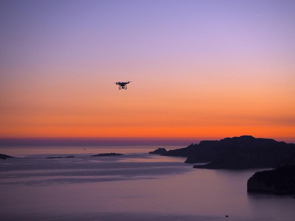 silhouette photo of drone on seashore