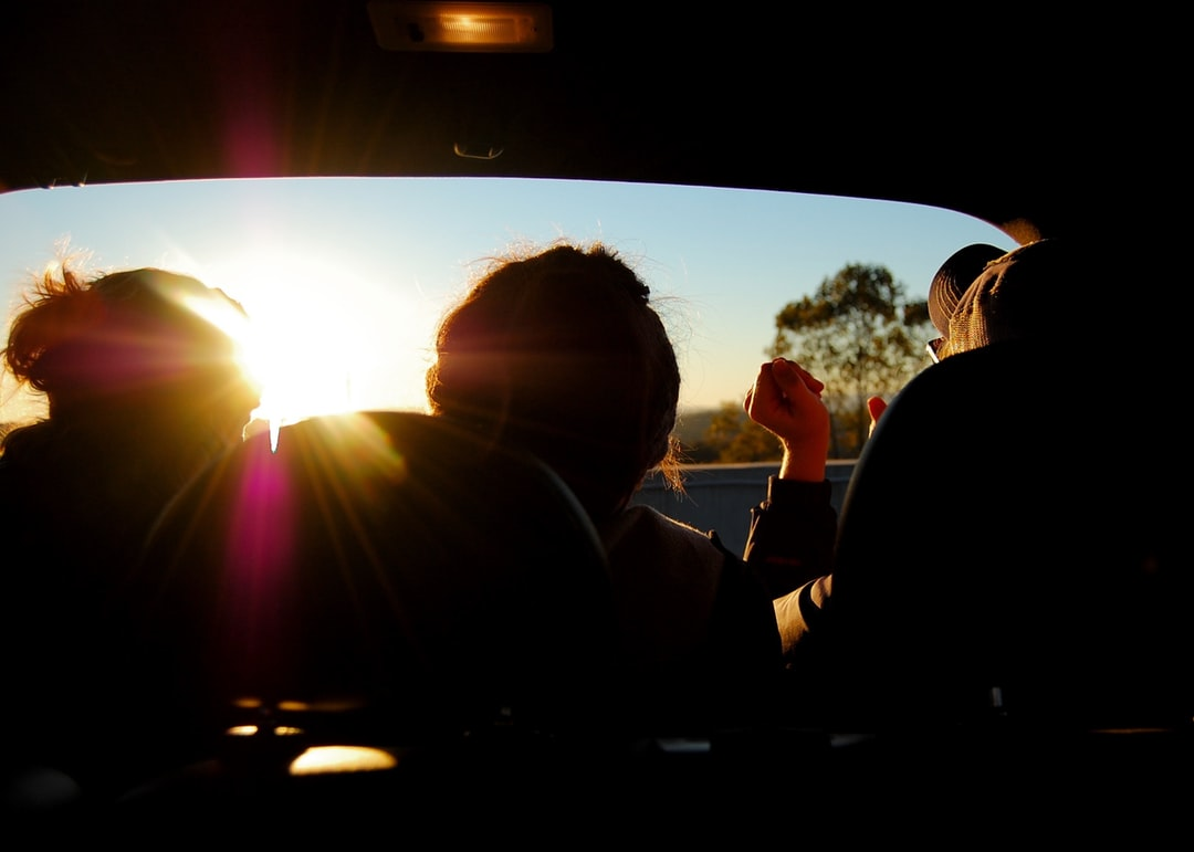 Three silhouettes of people hanging out in an opened trunk of a car watching the sunset