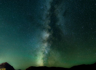long exposure shot of stars over black mountains milkyway teams background