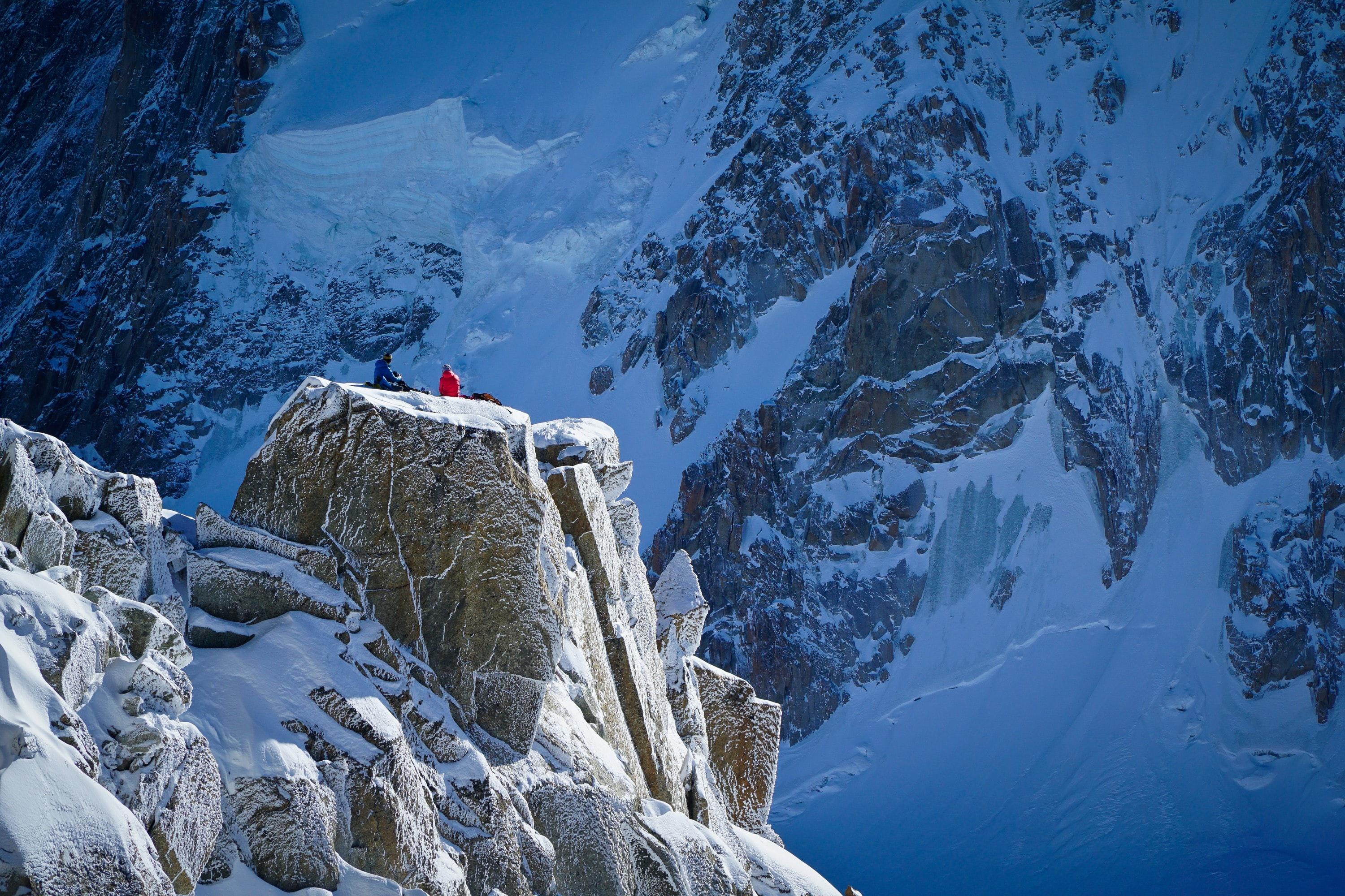 Two people wearing winter jackets sitting on a cliff on the side of a snowy mountain during winter in Chamonix