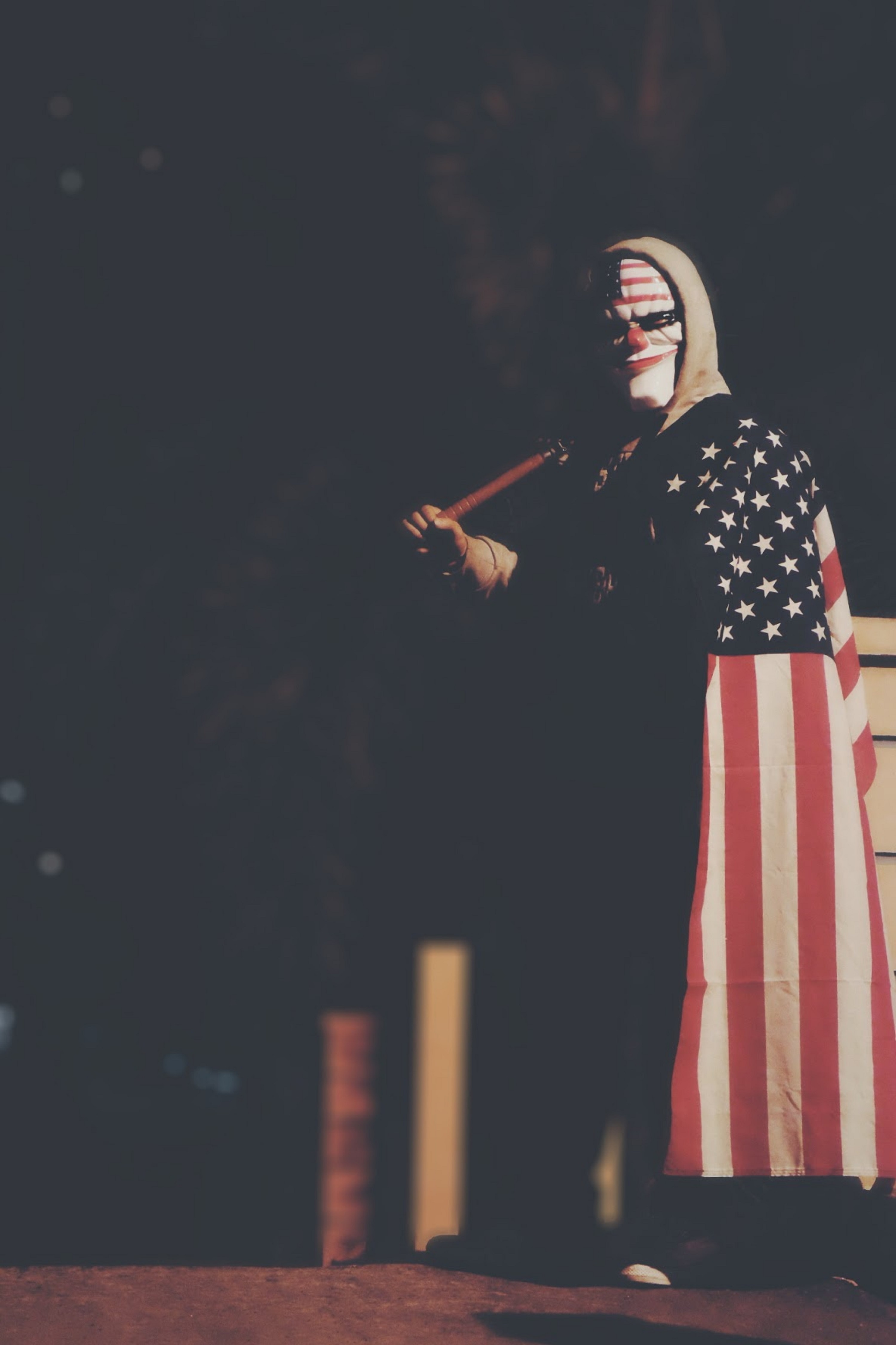 A figure costumed in an American flag, hoodie and mask